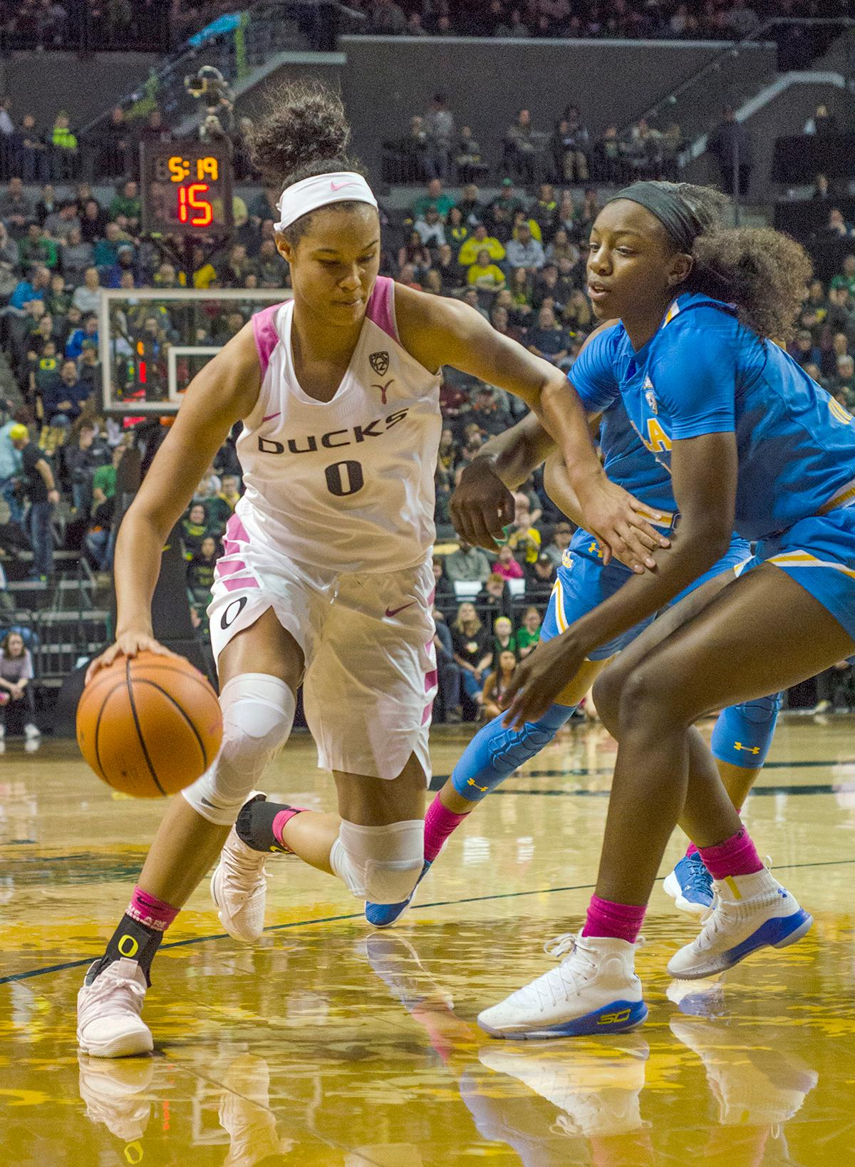 Oregon Ducks Satou Sabally (#00) drives past UCLA Bruins Michaela Onyenwere (#21). In front of a nearly sold out crowd of 7,098 very loud fans in Matt Knight Arena Monday night, the University of Oregon Women Ducks basketball team defeated UCLA 91-90 in overtime in their last game of the regular season. The Ducks are now 14-2 in conference play and UCLA falls to 12-4. Satou Sabally lead the way with 23 points, Maite Cazorla added 22, Sabrina Ionescu put up 16 and Ruthy Hebard ended the night with 14. At the end of the game graduating seniors Lexi Bando (#10) and Justine Hall (#3) were honored in a ceremony with Coach Kelly Graves and the team. Photo by Emily Gonzalez, Oregon News Lab