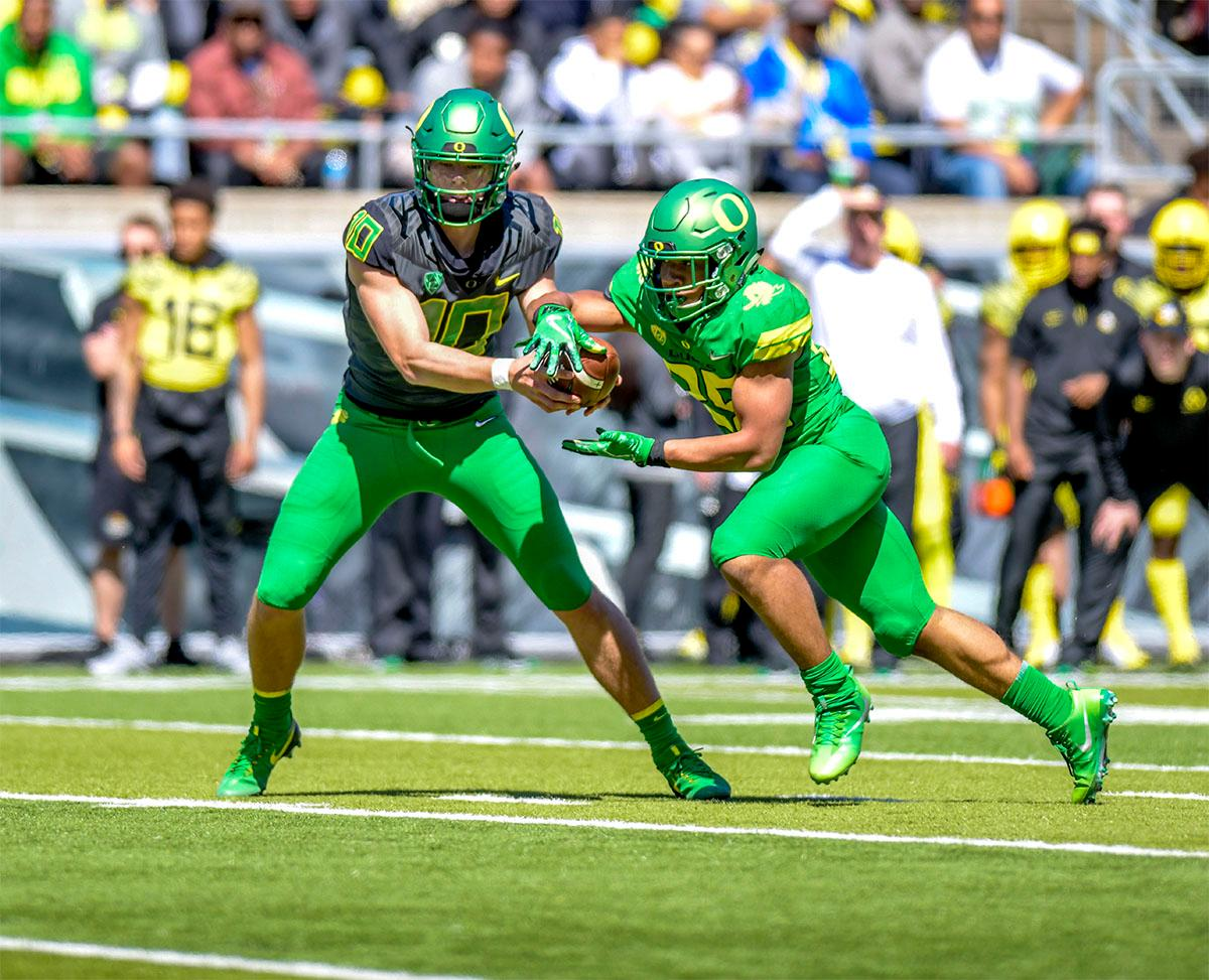 Justin Herbert (#10) passes the ball off to CJ Verde (#25). The Thunder defeated the Lightning 59-24 in the Spring Game on Saturday at Autzen Stadium. Photo by August Frank