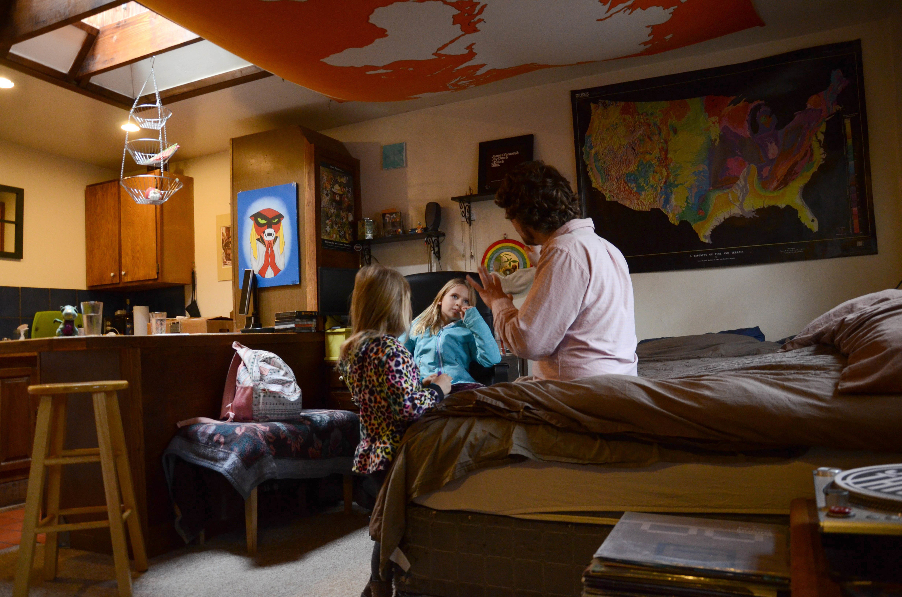FILE - In this Nov. 28, 2017, file photo, TC Bell sits with his two daughters Dagny, and Emma, before they get dressed for school, at their home in Denver. Bell's daughters were then recipients of the Children's Health Insurance Program or CHIP, which is a program that provides low-cost coverage to families who earn too much to qualify for Medicaid. Health care proposals are among the first actions for some new Democratic governors and Democratically controlled legislatures.   (AP Photo/Tatiana Flowers, File)