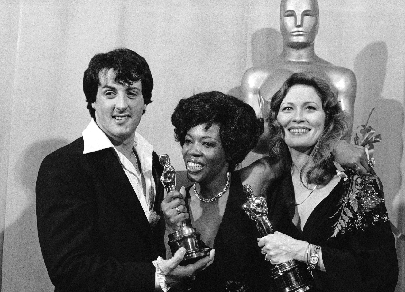 "HOLD FOR MONDAY, NOV. 21, STORY BY ERRIN HAINES WHACK – FILE – In this March 28, 1977, file photo, actor and screenwriter Sylvester Stallone, left, poses with Eletha Finch, center, widow of actor Peter Finch, and actress Faye Dunaway, right, at the Academy Awards in Los Angeles. Four decades after the Nov. 21, 1976, premiere of ""Rocky,"" the movie's reach is international, and the title character's underdog tale of determination, grit and sleepy-eyed charm still resonates with fans. (AP Photo, File)"