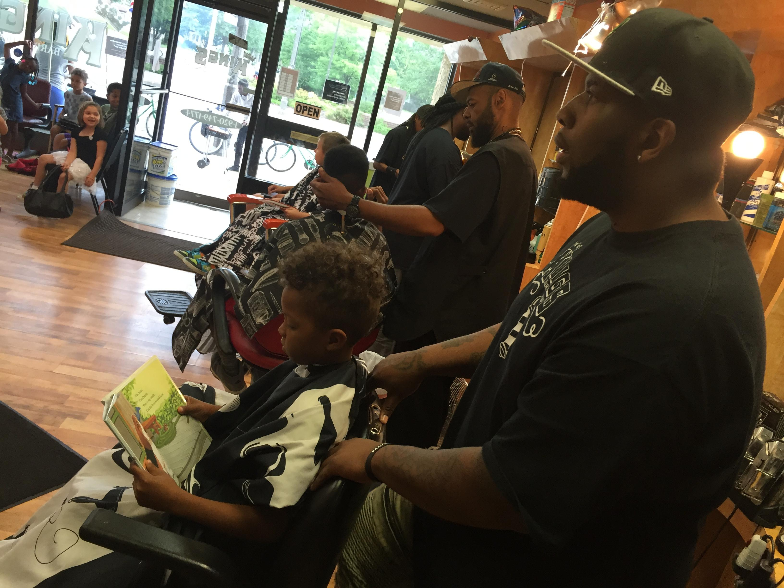 Daniel Gilbert, foreground, cuts hair for a child who is reading a book Aug. 28, 2017, at Kings Barber Shop in Appleton. (WLUK/Eric Peterson)