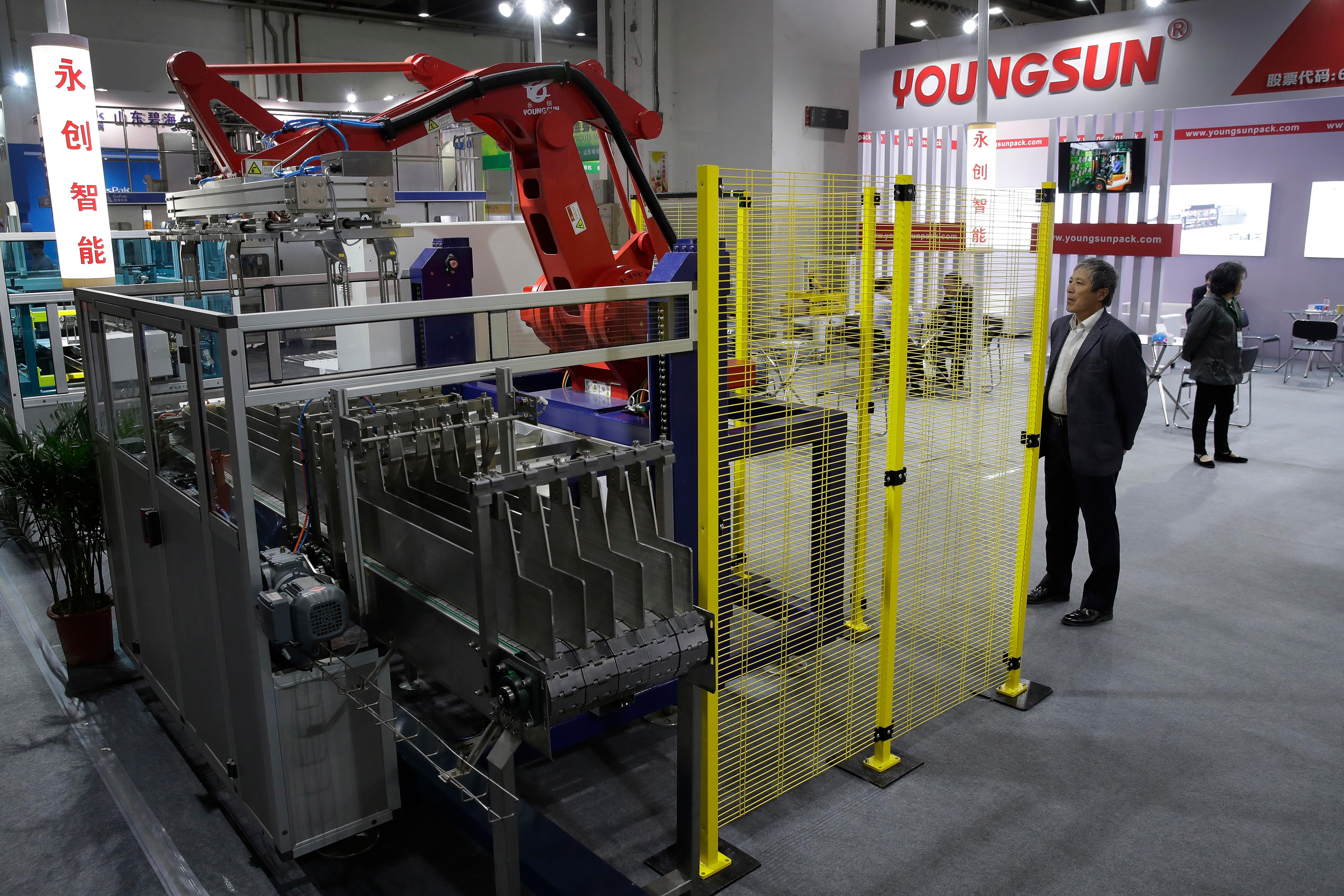 A man watches a Chinese company displaying a Chinese-made industrial robot demonstration on processing soybean at the International soybean exhibition in Shanghai, Thursday, April 12, 2018. China's government has denied President Xi Jinping's promises this week to cut import tariffs on cars and open China's markets wider were intended as an overture to settle a tariff dispute with Washington. A commerce ministry spokesman said negotiations were impossible under 'unilateral coercion' by President Donald Trump's government. (AP Photo/Andy Wong)