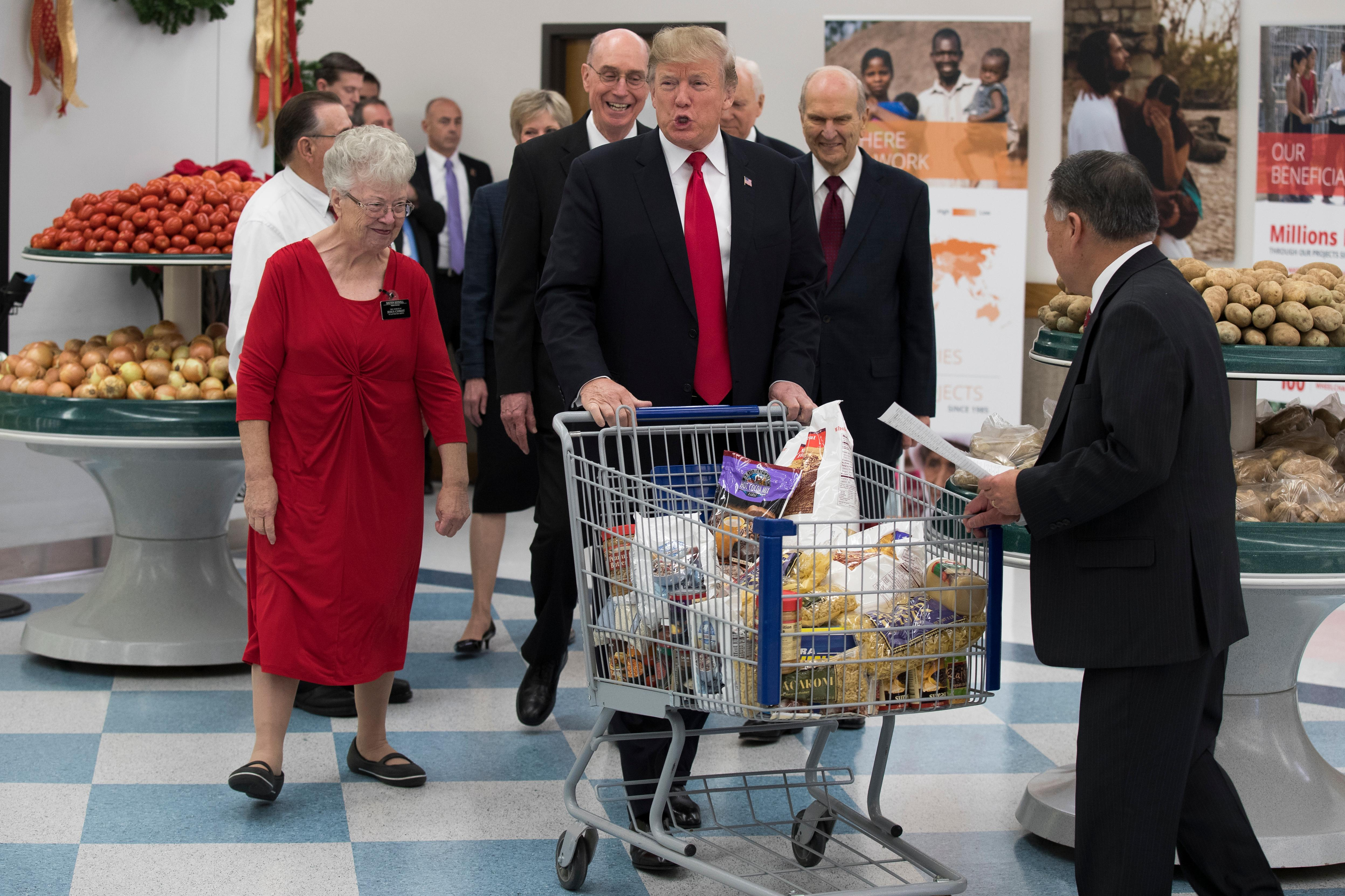 President Donald Trump pushes a cart during a tour of the Church of Jesus Christ of Latter-Day Saints Welfare Square food distribution center, Monday, Dec. 4, 2017, in Salt Lake City. (AP Photo/Evan Vucci)