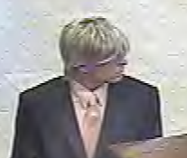"The suspect is described as a white man, 25-35 years old, 5'8"" %u2013 5'10"", 170 - 190 lbs., wearing a dark gray or black suit, light peach or pink shirt and tie, and blonde wig."