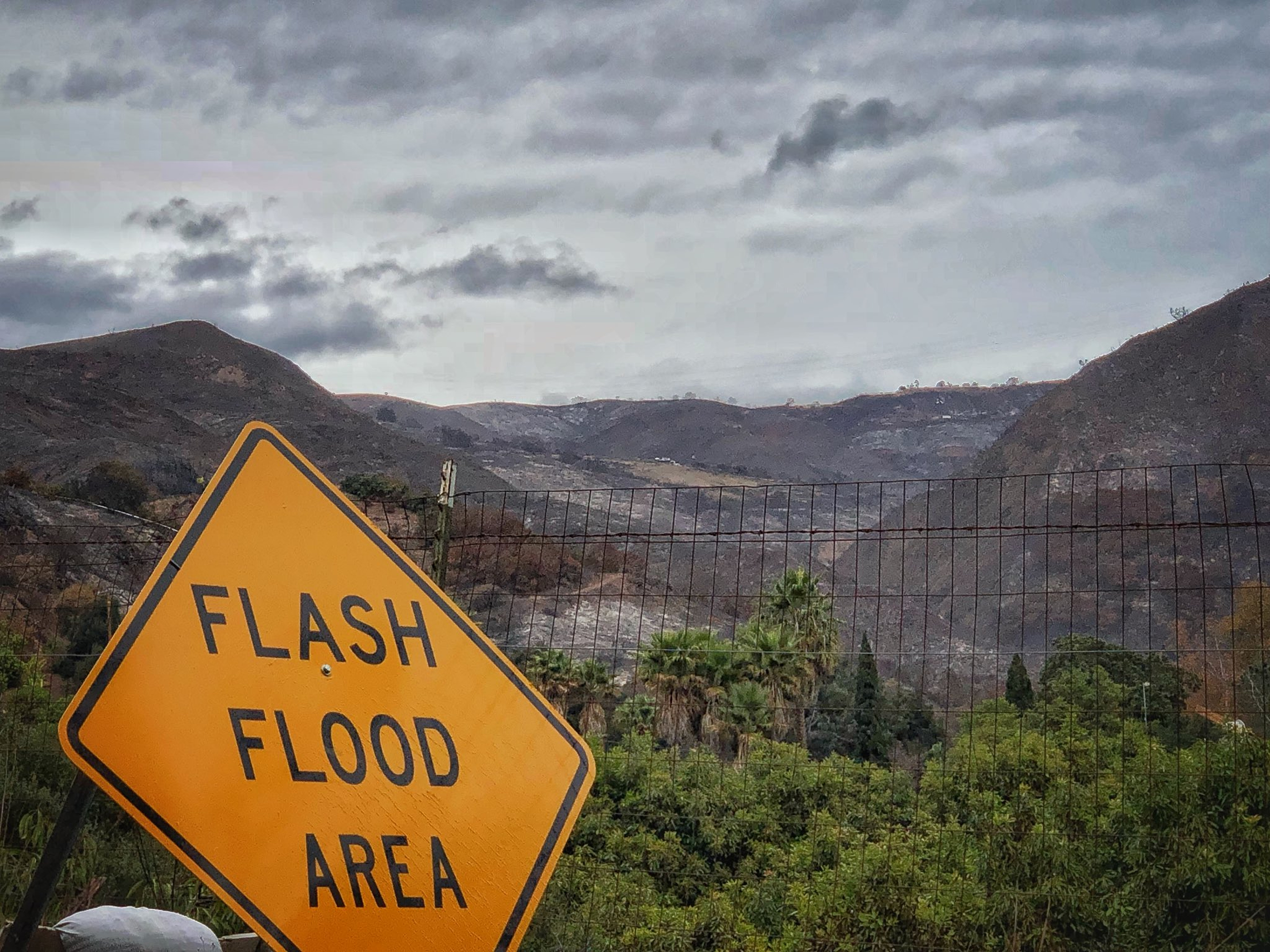 In this photo provided by Santa Barbara County Fire Department, a flash flood area sign is posted, as evacuations have been issued for several fire-ravaged communities in Santa Barbara, Calif., Monday, Jan. 8, 2018. Property owners stacked sandbags in devastated Northern California wine country Monday as authorities in Southern California ordered about 21,000 people to evacuate below hillsides burned by the state's largest wildfire in history. (Mike Eliason/Santa Barbara County Fire Department via AP)