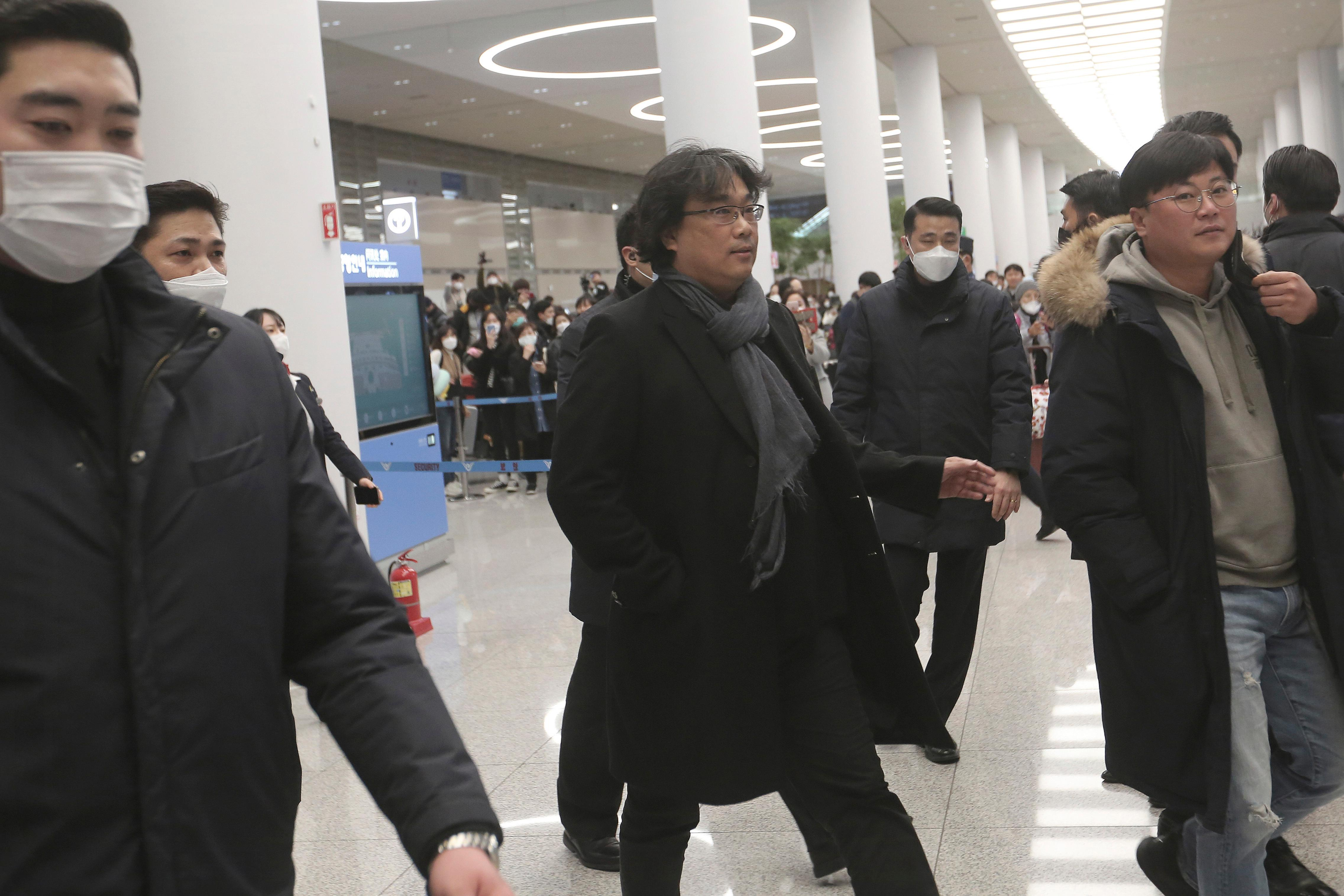 "South Korean director Bong Joon-ho, center, arrives at the Incheon International Airport in Incheon, South Korea, Sunday, Feb. 16, 2020. South Koreans are reveling in writer-director Bong's dark comic thriller, ""Parasite,"" which won this year's Academy Awards for best film and best international feature. The movie itself, however, doesn't put the country in a particularly positive light. (AP Photo/Ahn Young-joon)"