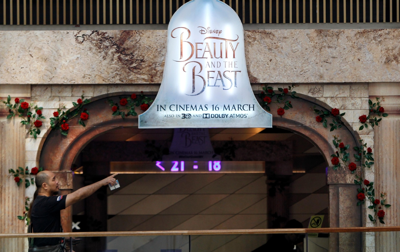 "A man walks in front of the a movie advertising board at shopping mall in Kuala Lumpur, Malaysia Tuesday, March 14, 2017.  Walt Disney has shelved the release of its new movie ""Beauty and the Beast"" in mainly Muslim Malaysia, even though film censors say Tuesday it has been approved with a minor cut involving a ""gay moment."" The country's two main cinema chains say the movie, due for screening Thursday, has been postponed indefinitely.(AP Photo/Daniel Chan)"