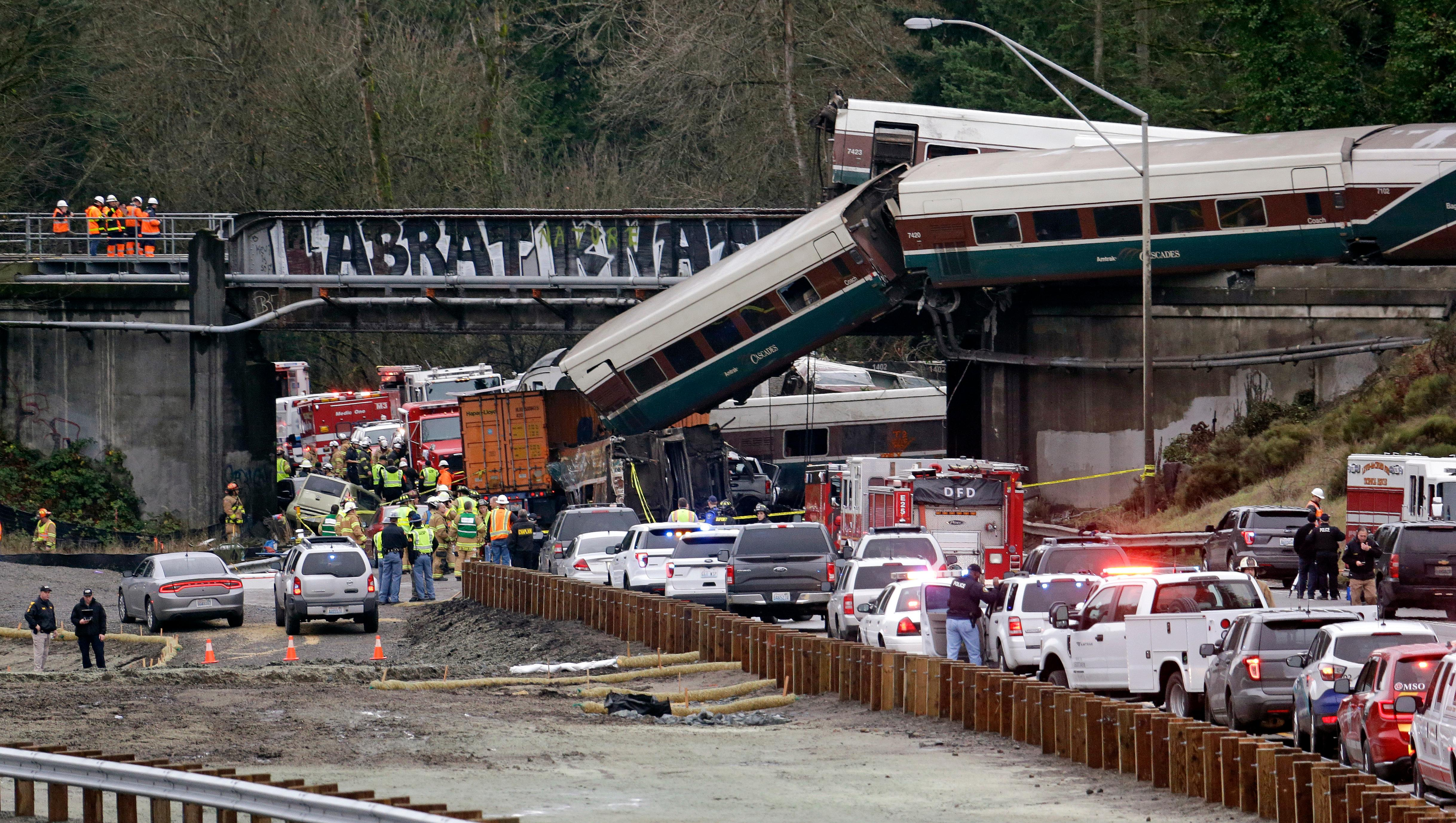 Cars from an Amtrak train lay spilled onto Interstate 5 below as some remain on the tracks above Monday, Dec. 18, 2017, in DuPont, Wash. The Amtrak train making the first-ever run along a faster new route hurtled off the overpass Monday near Tacoma and spilled some of its cars onto the highway below, killing some people, authorities said. Seventy-eight passengers and five crew members were aboard when the train moving at more than 80 mph derailed about 40 miles south of Seattle before 8 a.m., Amtrak said. (AP Photo/Elaine Thompson)