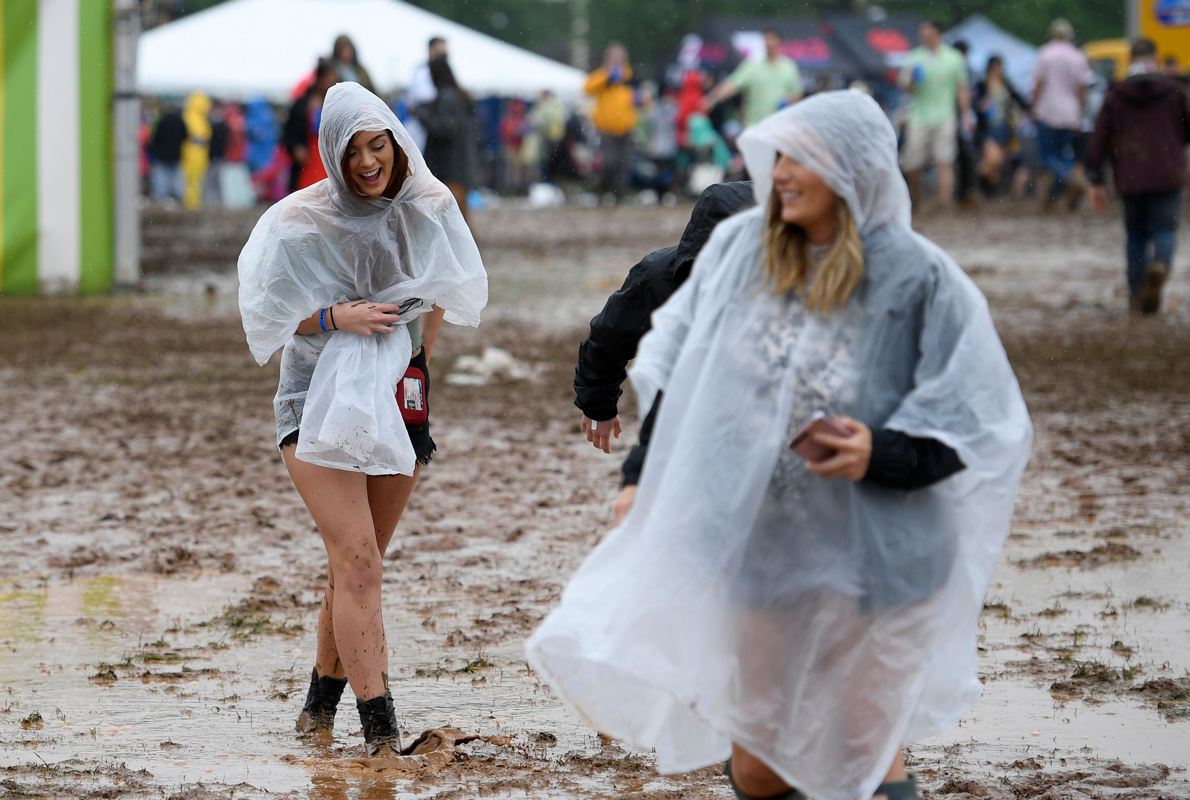 A woman walks through mud in the infield during the 143rd Preakness Stakes horse race at Pimlico race course, Saturday, May 19, 2018, in Baltimore. (AP Photo/Nick Wass)