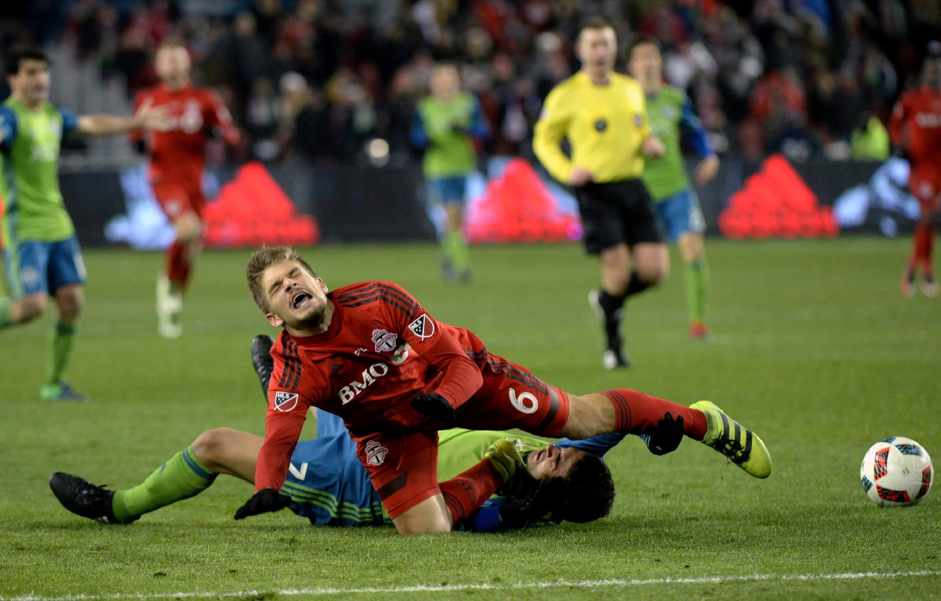 Toronto FC defender Nick Hagglund (6) takes down Seattle Sounders midfielder Cristian Roldan (7) during extra-time MLS Cup final soccer action in Toronto, Saturday, Dec. 10, 2016. (Nathan Denette/The Canadian Press via AP)