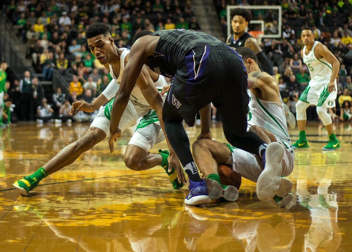 The Ducks and the Huskies fight for a loose ball. The Oregon Ducks defeated the Washington Huskies 65-40 on Thursday night at Matthew Knight Arena. Troy Brown, Junior led Oregon with 21 points to match his career high, and Kenny Wooten set a career best of seven shots blocked. The Ducks now stand 6-5 in the Pac-12 conference play. Photo by Abigail Winn, Oregon News Lab