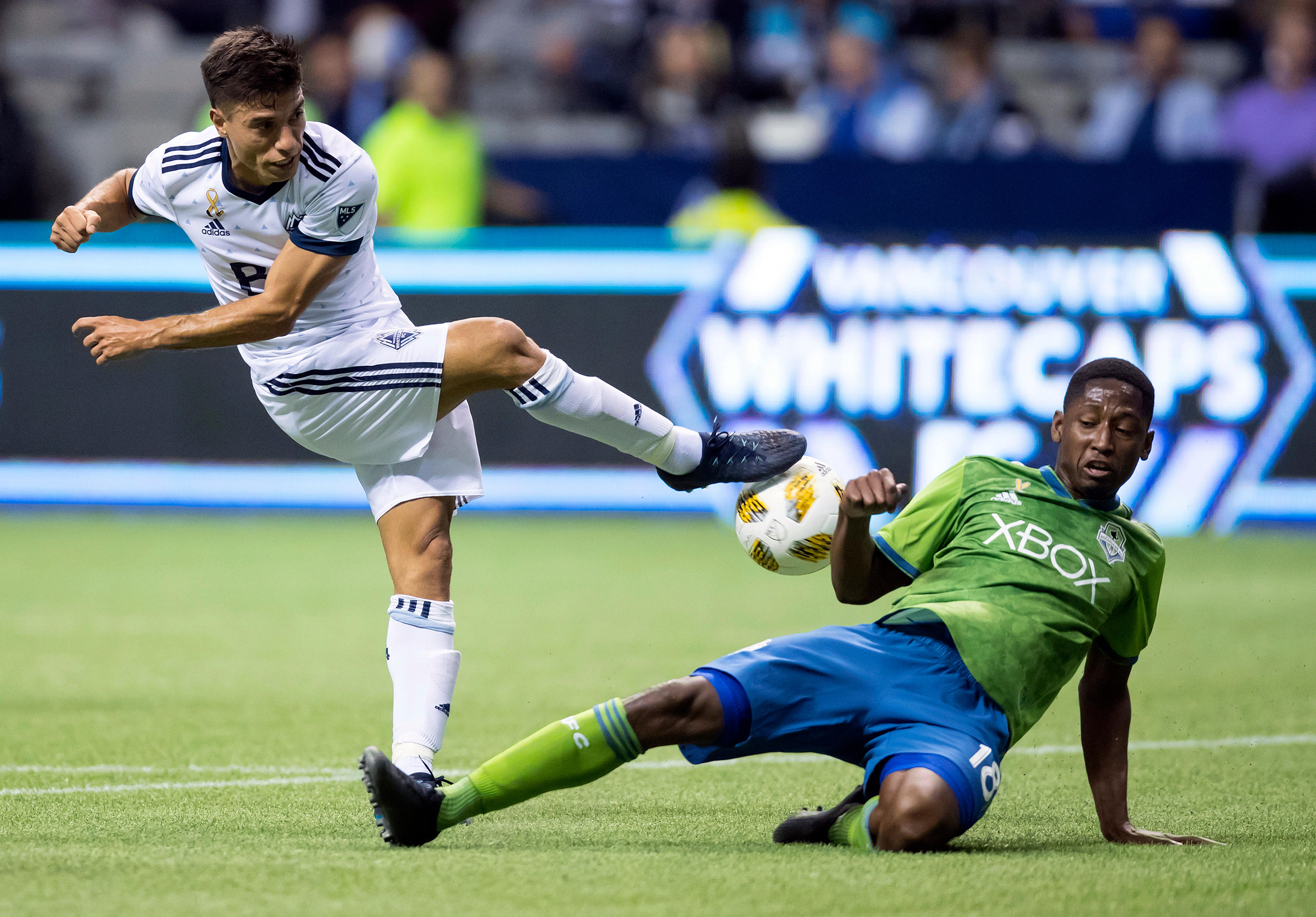 Vancouver Whitecaps' Nicolas Mezquida, left, has his shot blocked by Seattle Sounders' Kelvin Leerdam during the first half of an MLS soccer match, Saturday, Sept. 15, 2018, in Vancouver, British Columbia. (Darryl Dyck/The Canadian Press via AP)