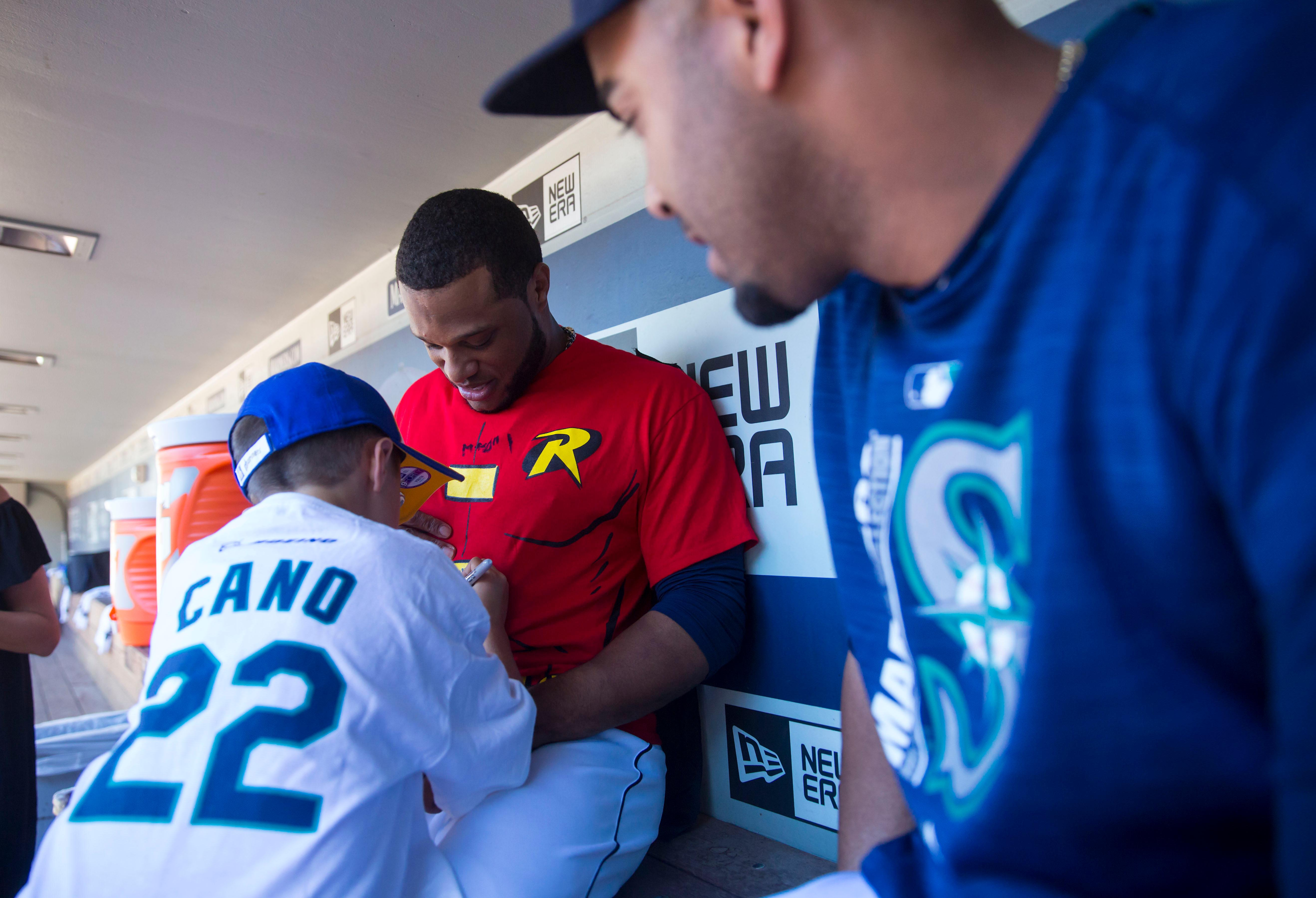 "Seven-year-old kidney cancer survivor Mason Nettleton signs Seattle Mariners Robinson Cano's superhero costume as Nettleton served Seattle as a ""Superhero for a Day"" on Tuesday, June 27, 2017. (Sy Bean/ Seattle Refined)"