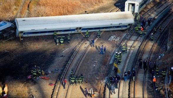 Firefighters and emergency rescuers swarm the scene near Spuyten Duyvil station in the Bronx, where train cars had flipped on their sides. One car was just feet away from the Harlem River.