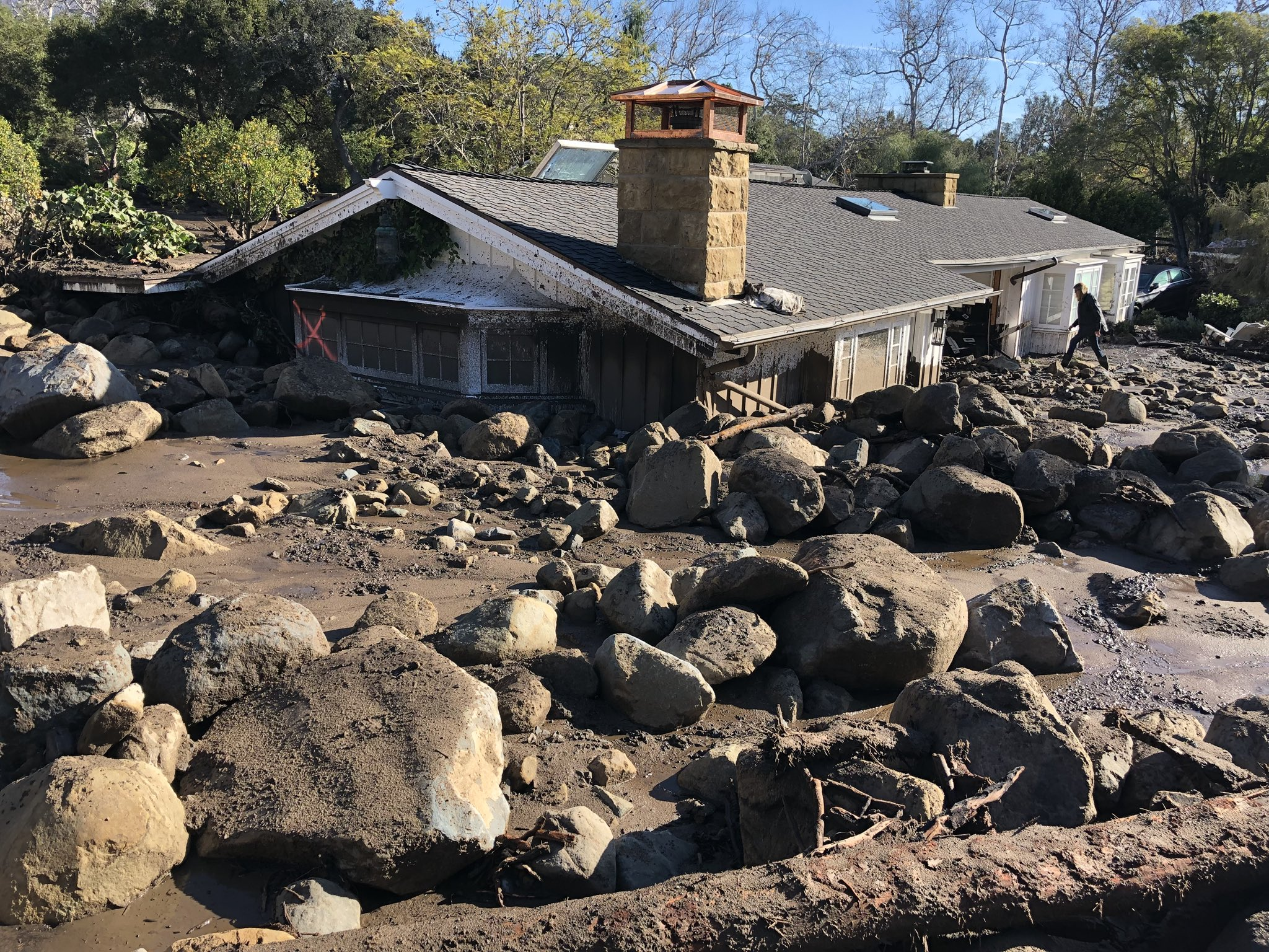 Kerry Mann navigates the large boulders and mudflow that destroyed the home of her friend in Montecito. The woman who lives in the home has not been seen since the early hours of Tuesday. (Photo & Caption: Mike Eliason, Santa Barbara County Fire Dept.)