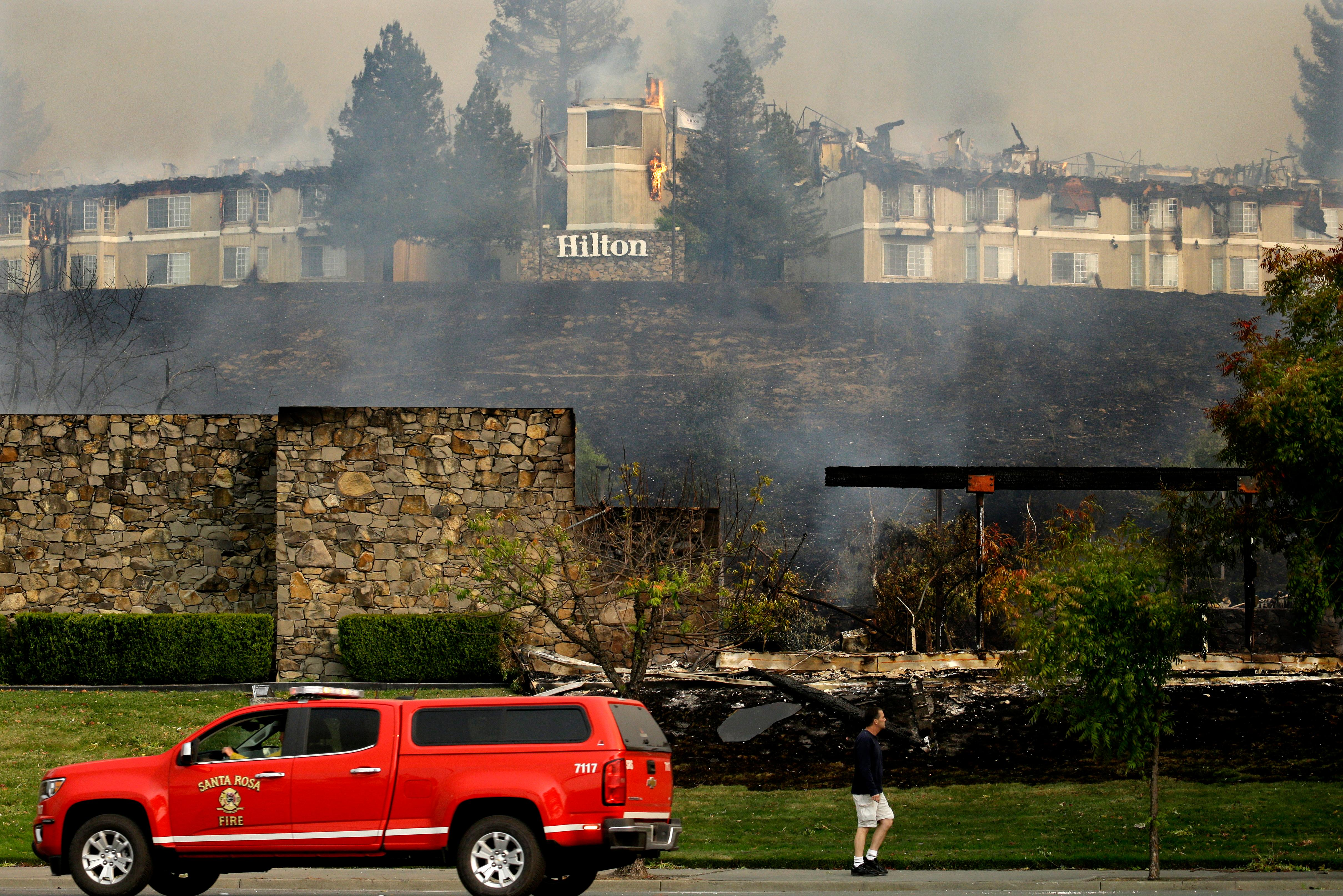 A fire burns at a Hilton hotel on Monday, Oct. 9, 2017, in Santa Rosa, Calif. Wildfires whipped by powerful winds swept through Northern California sending residents on a headlong flight to safety through smoke and flames as homes burned. (AP Photo/Ben Margot)