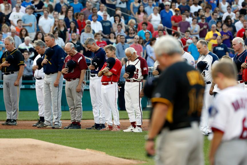 Members of both congressional teams bow their heads for a moment of silence for Rep. Steve Scalise, R-La., before the Congressional baseball game, Thursday, June 15, 2017, in Washington. The annual GOP-Democrats baseball game raises money for charity. (AP Photo/Alex Brandon)