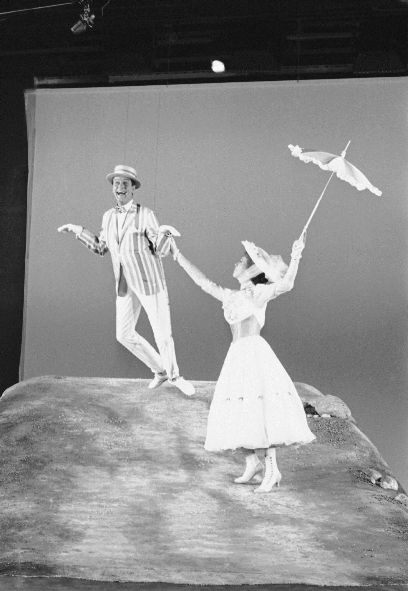 "FILE - In this June 25, 1963, file photo, Dick Van Dyke, left, is airborne during a dance with Julie Andrews, right, during the filming of ""Mary Poppins"" in Los Angeles. The 91-year-old Van Dyke confirmed to several outlets on Dec. 19, 2016, that he will appear in an upcoming sequel to the 1964 film. (AP Photo/Don Brinn, File)"