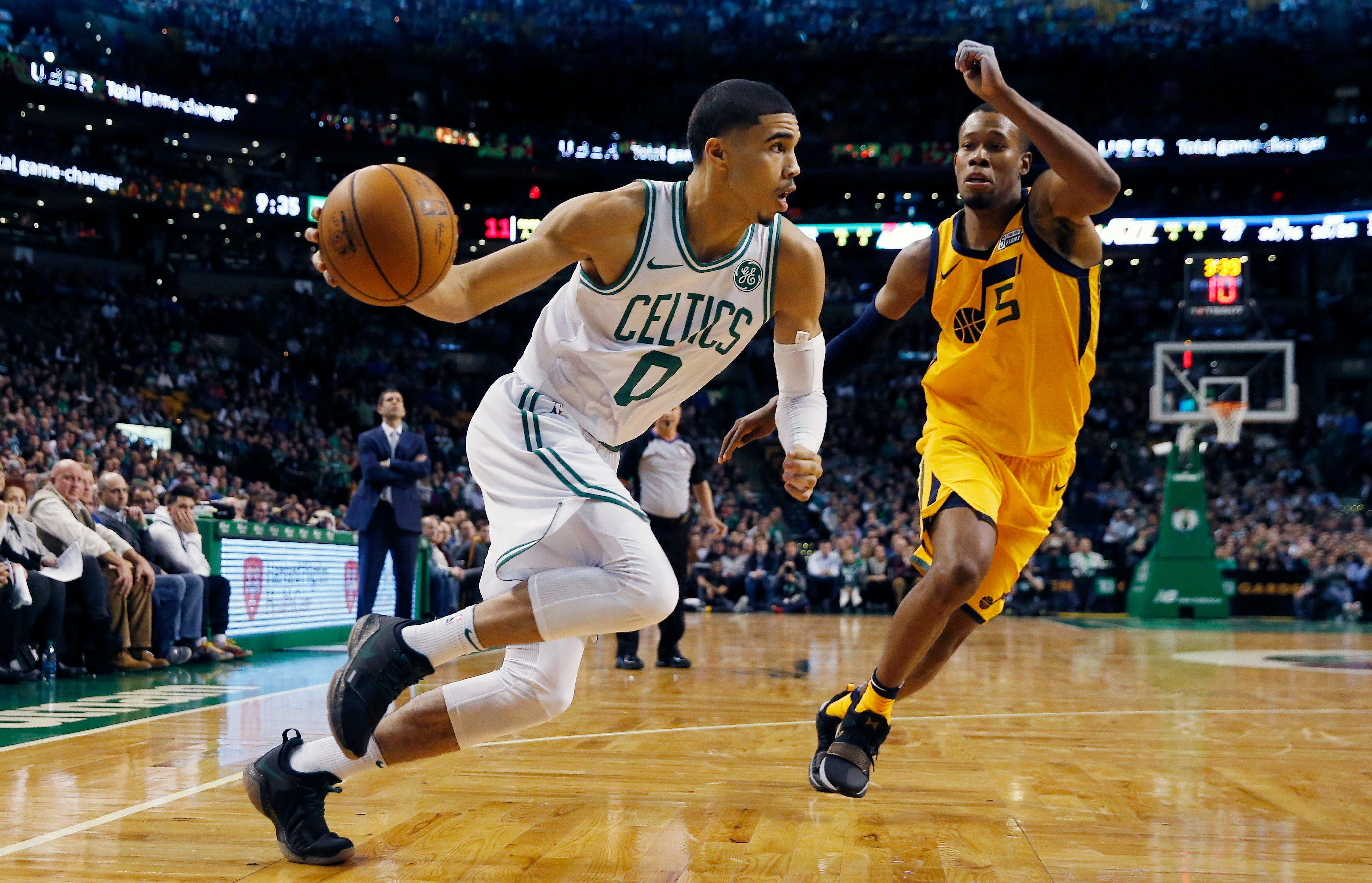 Boston Celtics' Jayson Tatum (0) drives past Utah Jazz's Rodney Hood (5) during the fourth quarter of an NBA basketball game in Boston, Friday, Dec. 15, 2017. The Jazz won 107-95. (AP Photo/Michael Dwyer)