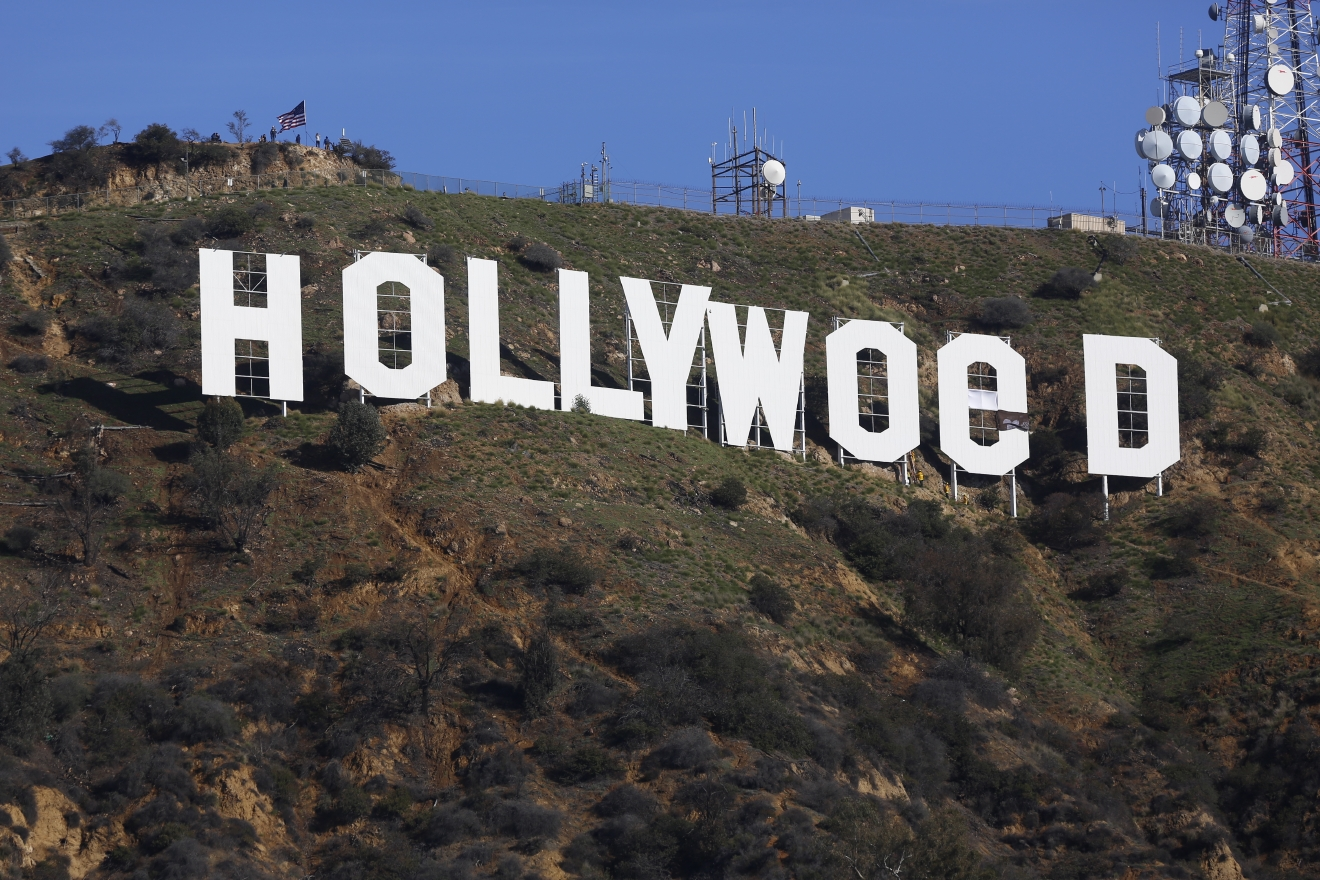 "Los Angeles County firemen remove banners from the letters on the Hollywood sign, seen vandalized Sunday, Jan. 1, 2017. Los Angeles residents awoke New Year's Day to find a prankster had altered the famed Hollywood sign to read ""HOLLYWeeD."" Police have notified the city's Department of General Services, whose officers patrol Griffith Park and the area of the rugged Hollywood Hills near the sign. California voters in November approved Proposition 64, which legalized the recreational use of marijuana, beginning in 2018. (AP Photo/Damian Dovarganes)"