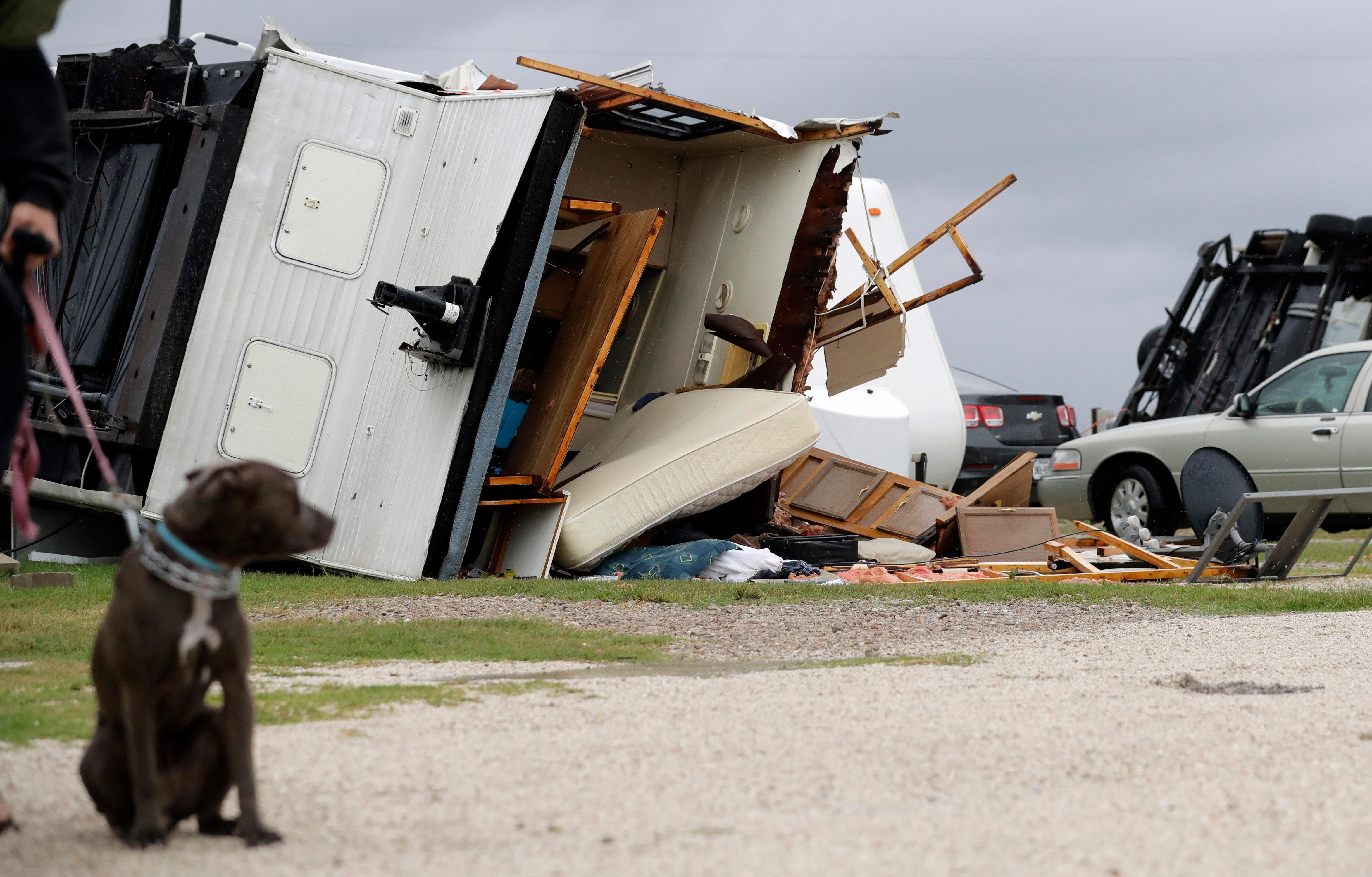 A trailer overturned in the wake of Hurricane Harvey lies on it's side, Saturday, Aug. 26, 2017, in Aransas Pass, Texas.  Harvey rolled over the Texas Gulf Coast on Saturday, smashing homes and businesses and lashing the shore with wind and rain so intense that drivers were forced off the road because they could not see in front of them.  (AP Photo/Eric Gay)
