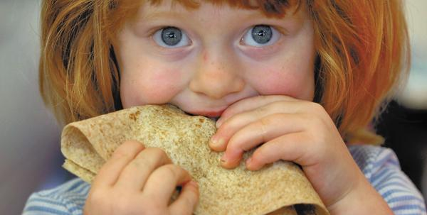 Jasmine Hogue, 3, tackles a tortilla during the summer lunch program in the Jackson Elementary School cafeteria Wednesday. Young people ages 1 to 18 are eligible for free meals through the program, regardless of family income. - Bob Pennell