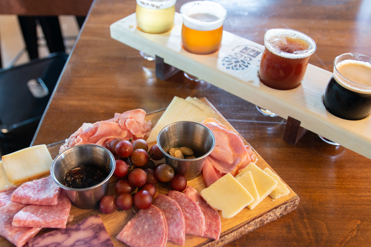 Charcuterie board with a beer flight featuring Arms Length, Napoleon's Revenge Belgian Tripel, Lancaster English Strong Ale, and Left Hand's Milk Stout Nitro{ }/ Image: Elizabeth A. Lowry // Published: 7.20.20