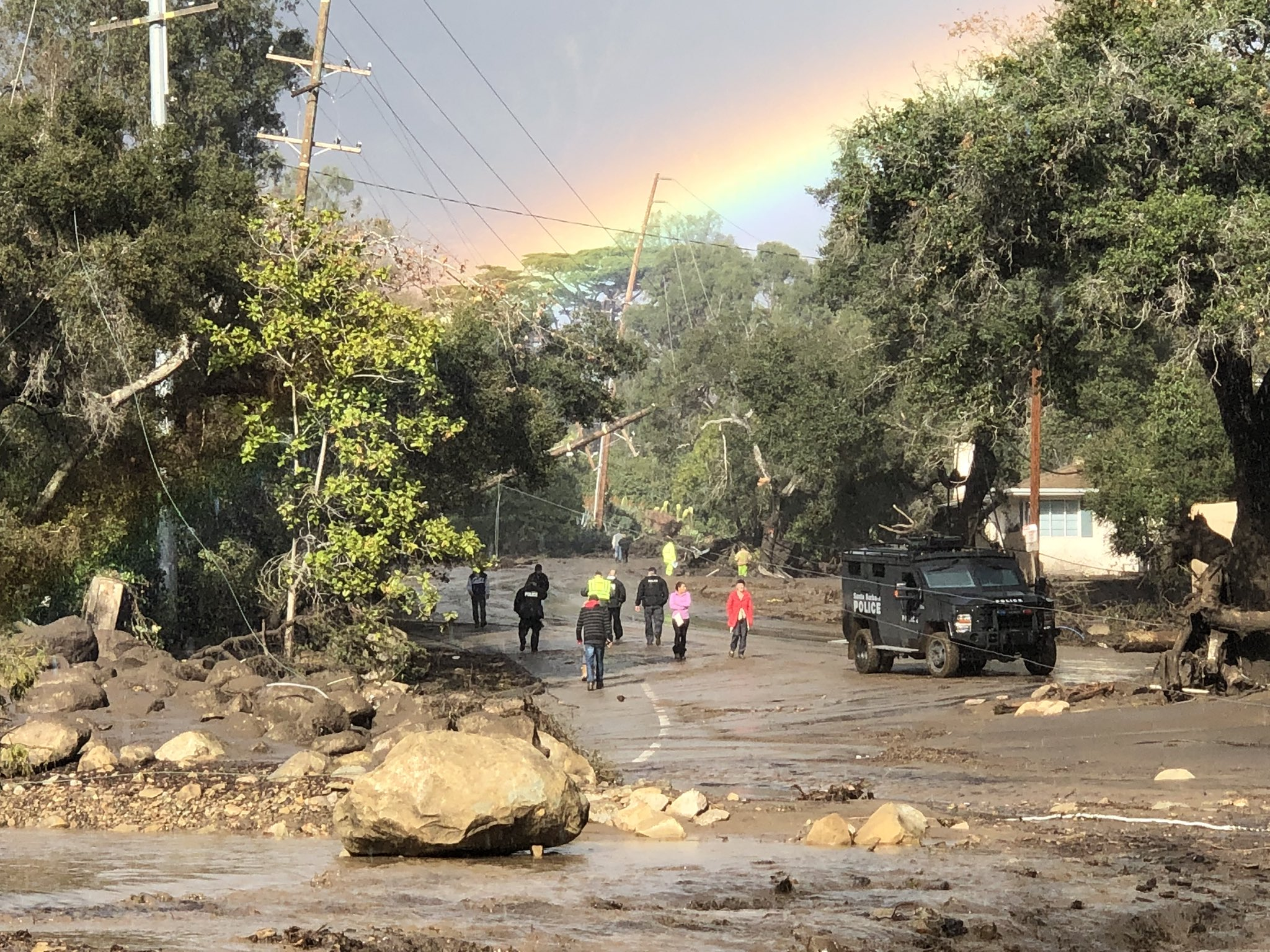A rainbow forms above Montecito while law enforcement and the curious survey the destruction on Hot Springs Road in Montecito. Deadly overnight mudflow and debris destroyed several homes in the area.{ }(Photo & Caption: Mike Eliason, Santa Barbara County Fire Dept.)