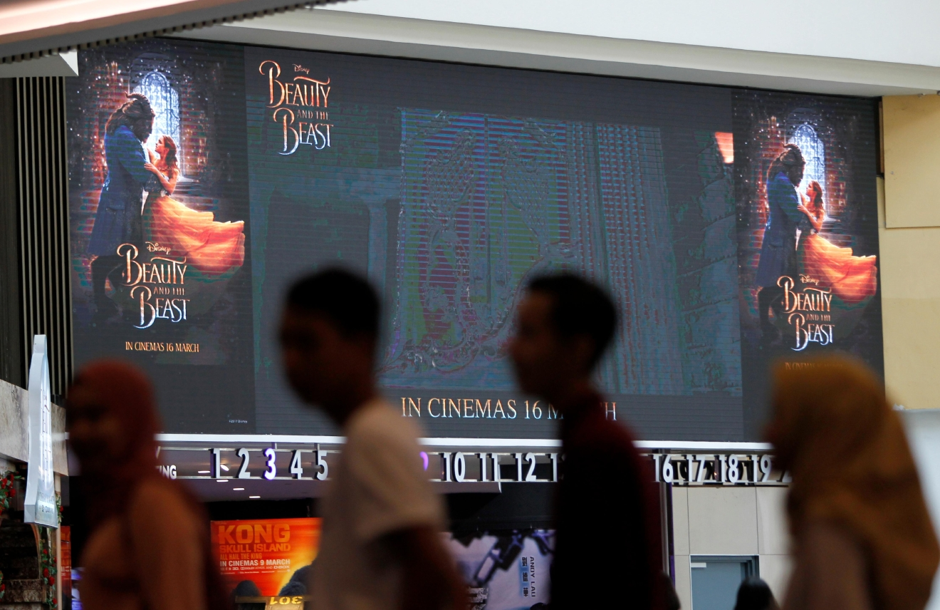 "People wait in queue to counter inside cinema at shopping mall in Kuala Lumpur, Malaysia on Tuesday, March 14, 2017. Walt Disney has shelved the release of its new movie ""Beauty and the Beast"" in mainly Muslim Malaysia, even though film censors said Tuesday it had been approved with a minor cut involving a ""gay moment."" (AP Photo/Daniel Chan)"