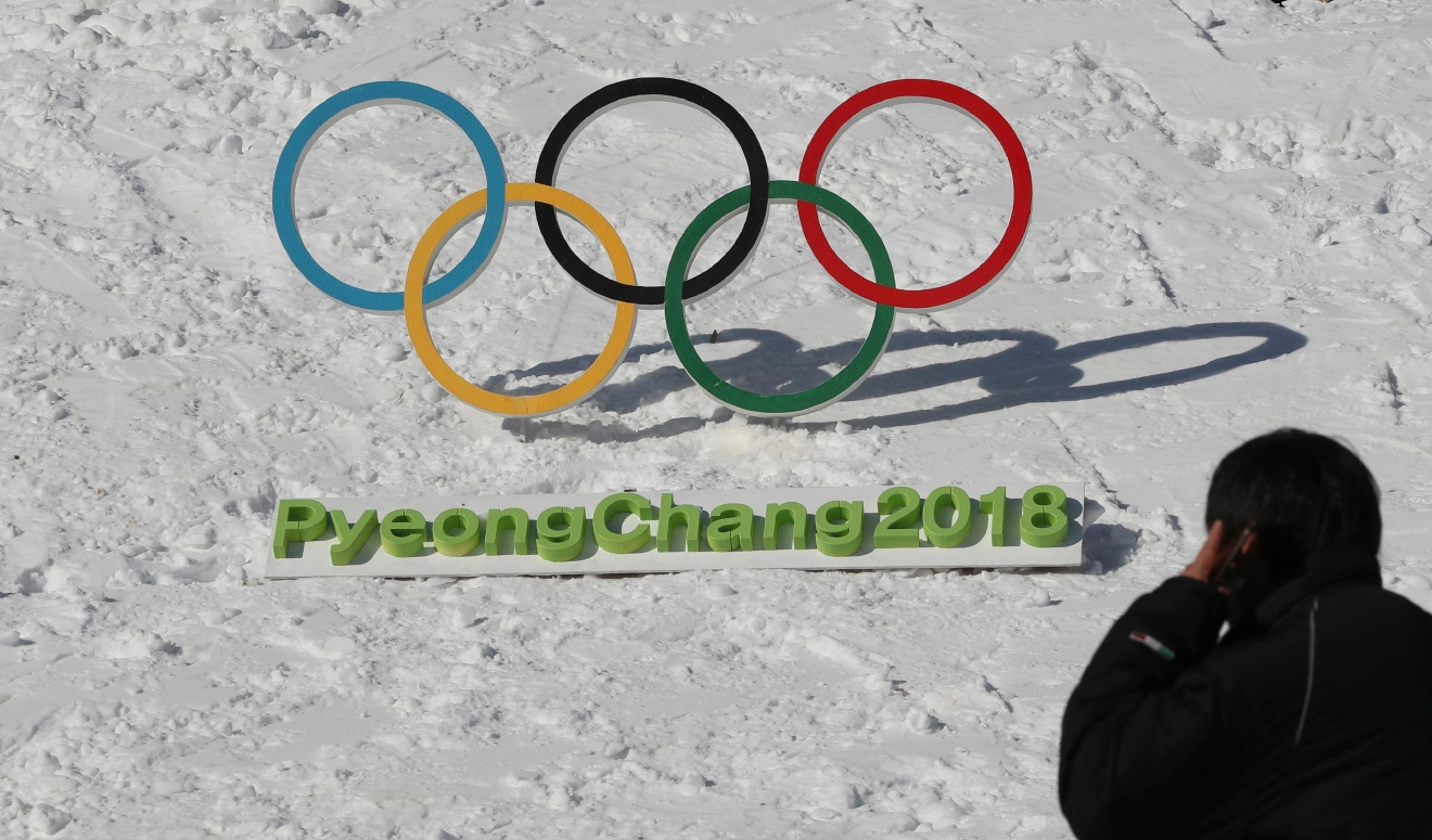 In this Friday, Feb. 3, 2017 photo, a man walks by the Olympic rings with a sign of 2018 Pyeongchang Olympic Winter Games in Pyeongchang, South Korea. One year before the Olympics, the country is in political disarray, and winter sports are the last thing on many people's minds. To say that South Koreans are distracted from what had been billed as a crowning sports achievement is an understatement. (AP Photo/Lee Jin-man)