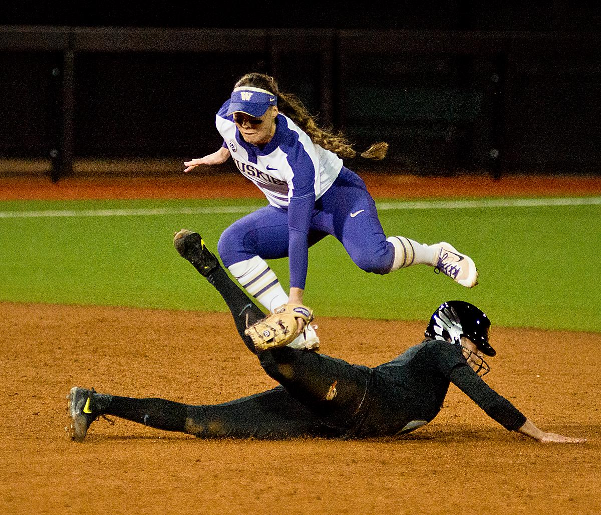 Ducks Nikki Urida (#3) slides safely into second base as Huskies Sis Bates (#22) is unable to secure the throw.  In Game Two of a three-game series, the University of Oregon Ducks softball team defeated the University of Washington Huskies 4-1 Friday night in Jane Sanders Stadium. Danica Mercado (#2), Alexis Mack (#10) and Mia Camuso (#7) all scored in the win, Mack twice. The Ducks play the Huskies for the tie breaker on Saturday with the first pitch at noon. Photo by Dan Morrison, Oregon News Lab
