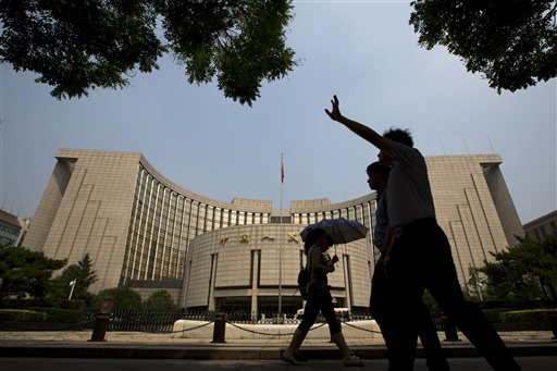 People walk past China's central bank or People's Bank of China in Beijing Tuesday.
