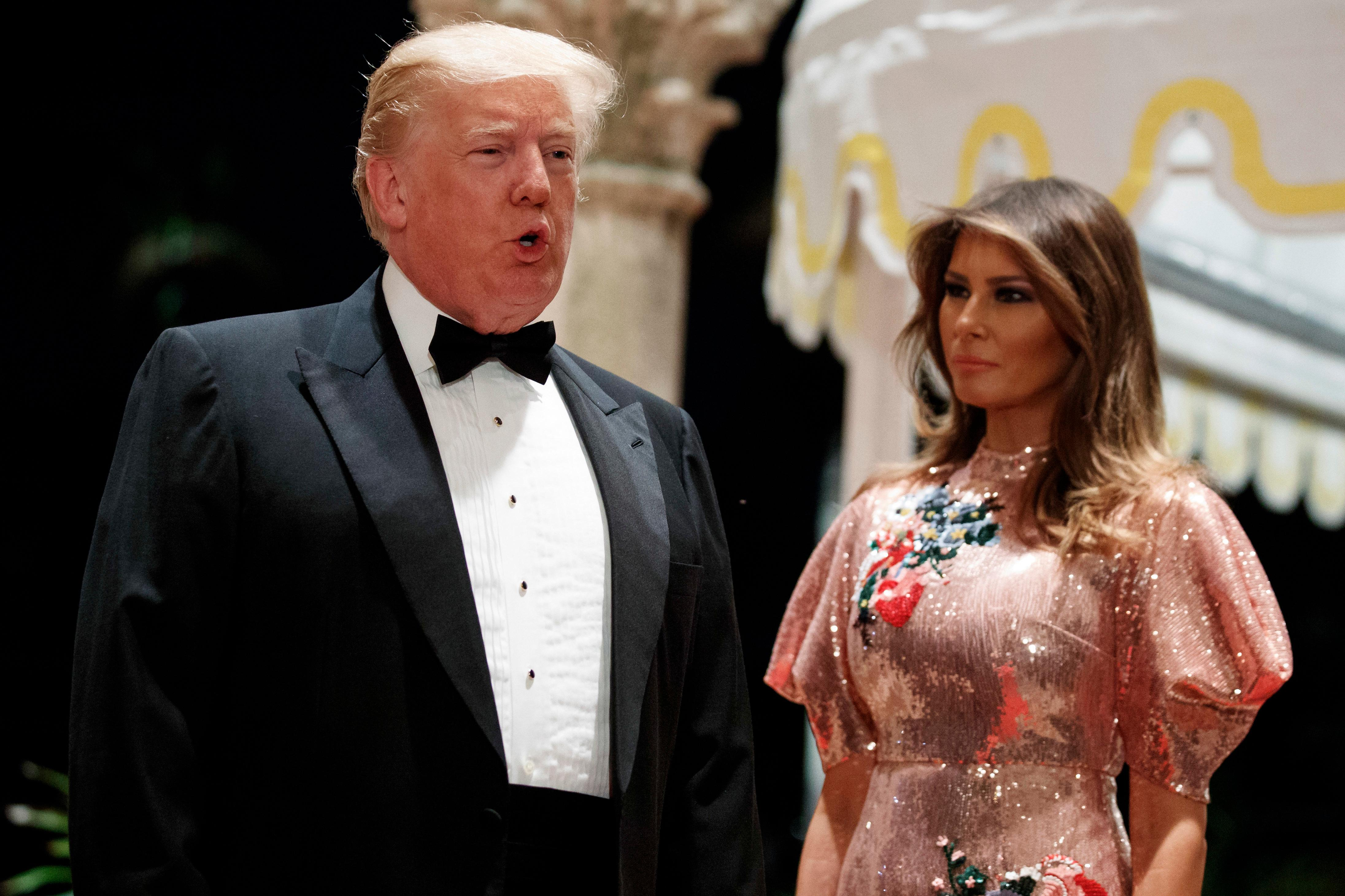 First lady Melania Trump looks on as President Donald Trump speaks with reporters after arriving for a New Year's Eve gala at his Mar-a-Lago resort, Sunday, Dec. 31, 2017, in Palm Beach, Fla. (AP Photo/Evan Vucci)