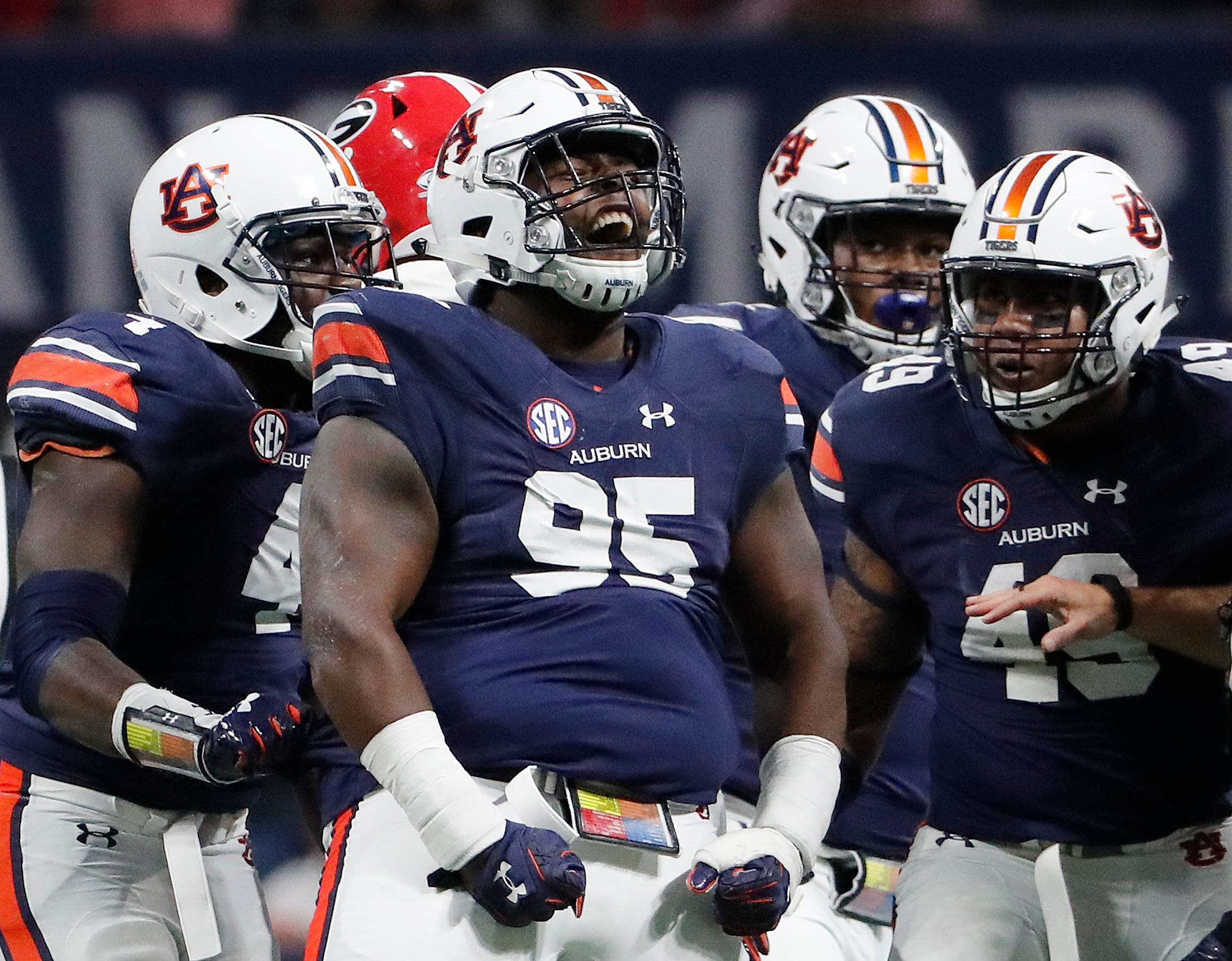 Auburn defensive lineman Dontavius Russell (95) celebrates tackling Georgia quarterback Jake Fromm during the first half of the Southeastern Conference championship NCAA college football game, Saturday, Dec. 2, 2017, in Atlanta. (AP Photo/David Goldman)