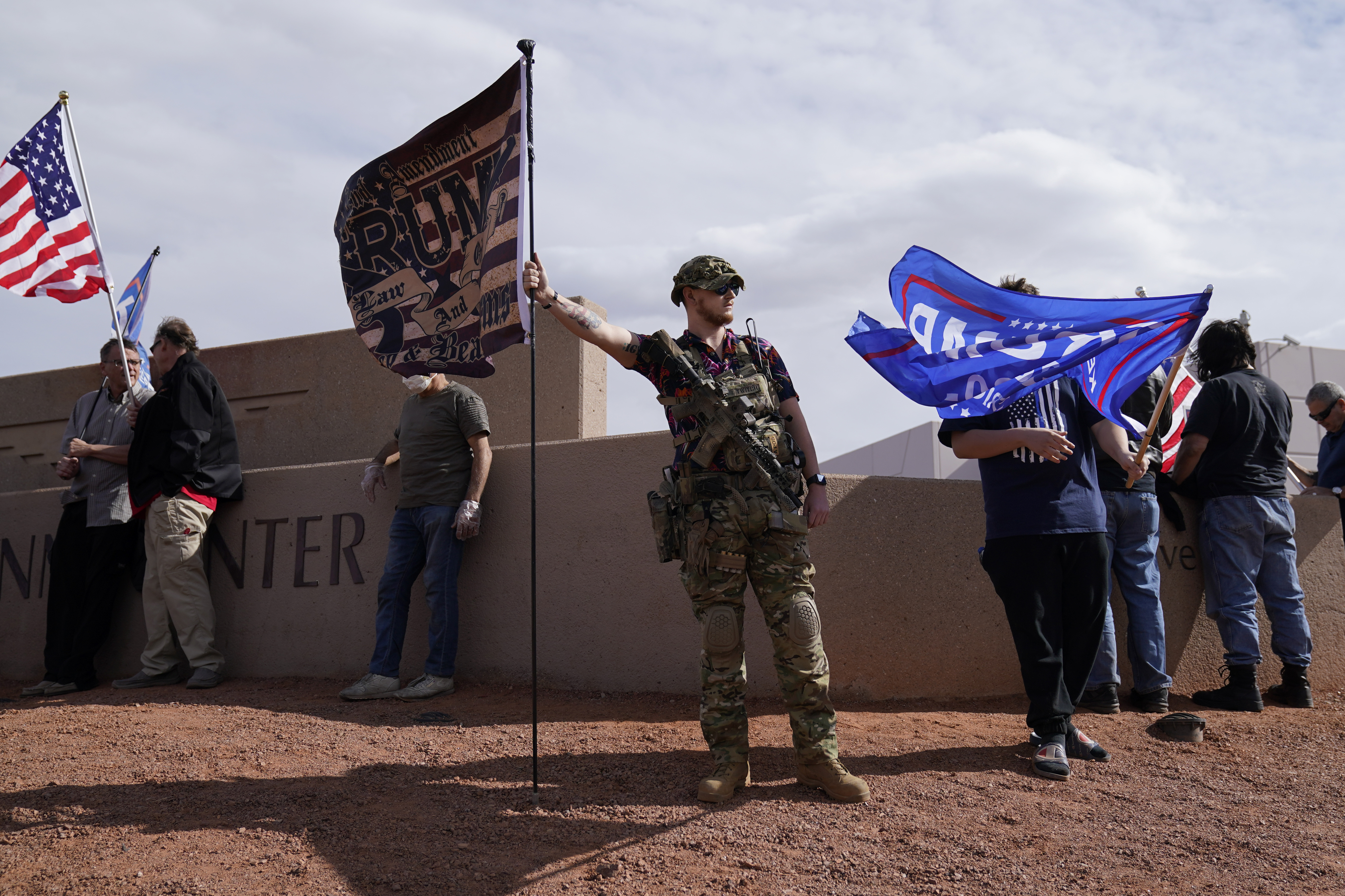 An armed supporter of President Donald Trump holds a flag while standing with others outside of the Clark County Elections Department in North Las Vegas, Nev., Saturday, Nov. 7, 2020. Democrat Joe Biden defeated President Donald Trump to become the 46th president of the United States on Saturday, positioning himself to lead a nation gripped by the historic pandemic and a confluence of economic and social turmoil. (AP Photo/John Locher)