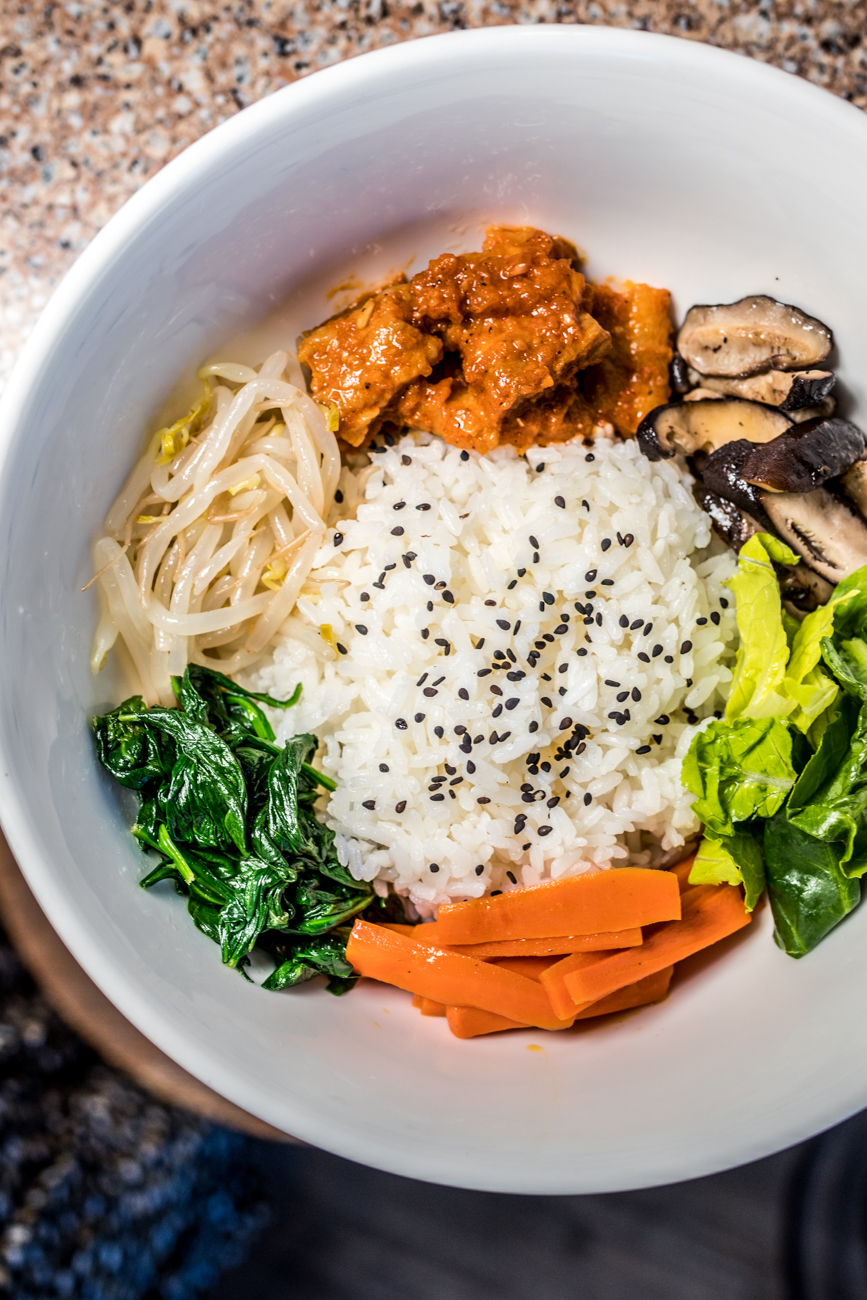 "Bibimbap: a Korean classic and comfort food that translates to ""mixed rice"" rice featuring lettuce, pork belly, shiitake mushrooms, caramelized onions, spinach, carrots, bean sprouts, and gochujang red pepper paste / Image: Catherine Viox // Published: 1.8.20"