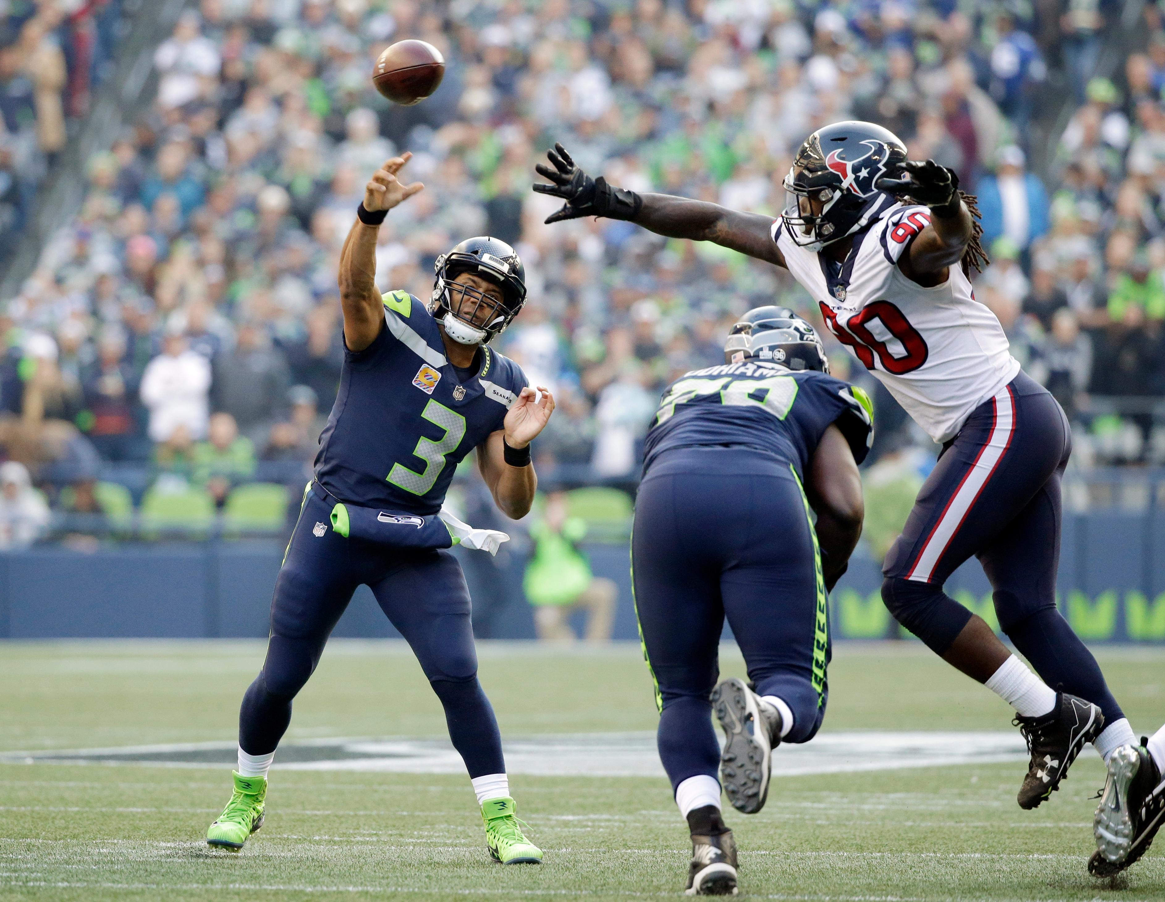 Seattle Seahawks quarterback Russell Wilson (3) passes under pressure from Houston Texans outside linebacker Jadeveon Clowney (90) in the second half of an NFL football game, Sunday, Oct. 29, 2017, in Seattle. (AP Photo/Elaine Thompson)