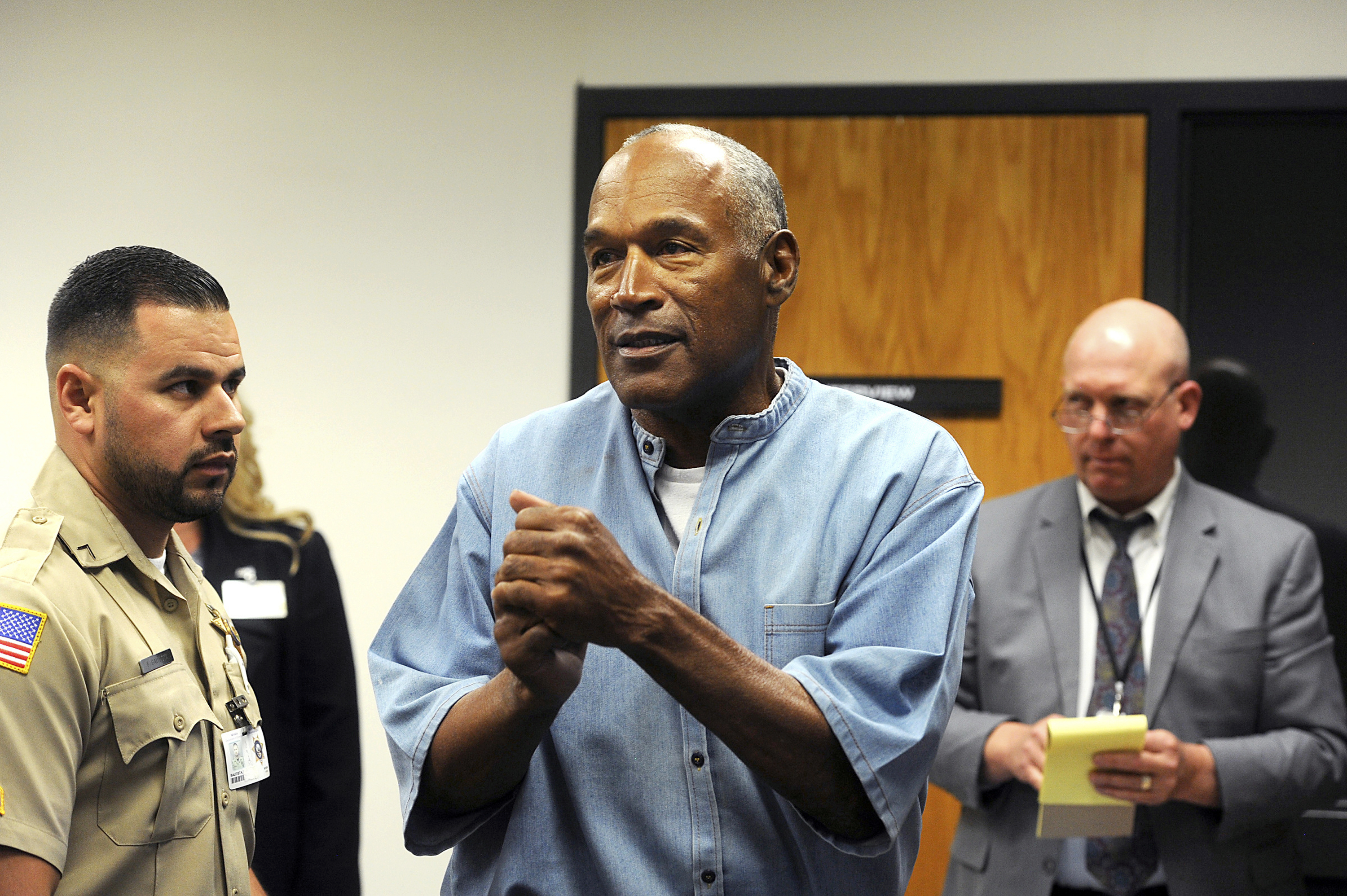 FILE - In this July 20, 2017 file photo, former NFL football star O.J. Simpson reacts after learning he was granted parole during a hearing at the Lovelock Correctional Center in Lovelock, Nev. Simpson was granted parole after more than eight years in prison for a Las Vegas hotel heist. A Nevada prison official said early Sunday, Oct. 1, 2017, O.J. Simpson, the former football legend and Hollywood star, has been released from a Nevada prison in Lovelock after serving nine years for armed robbery.  (Jason Bean/The Reno Gazette-Journal via AP, Pool, File)