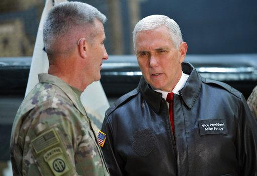 U.S. Vice President Mike Pence speaks to Gen. Nick Nicholson, commander of U.S. forces in Afghanistan, in a hangar at Bagram Air Base in Afghanistan on Thursday, Dec. 21, 2017. (Mandel Ngan/Pool via AP)