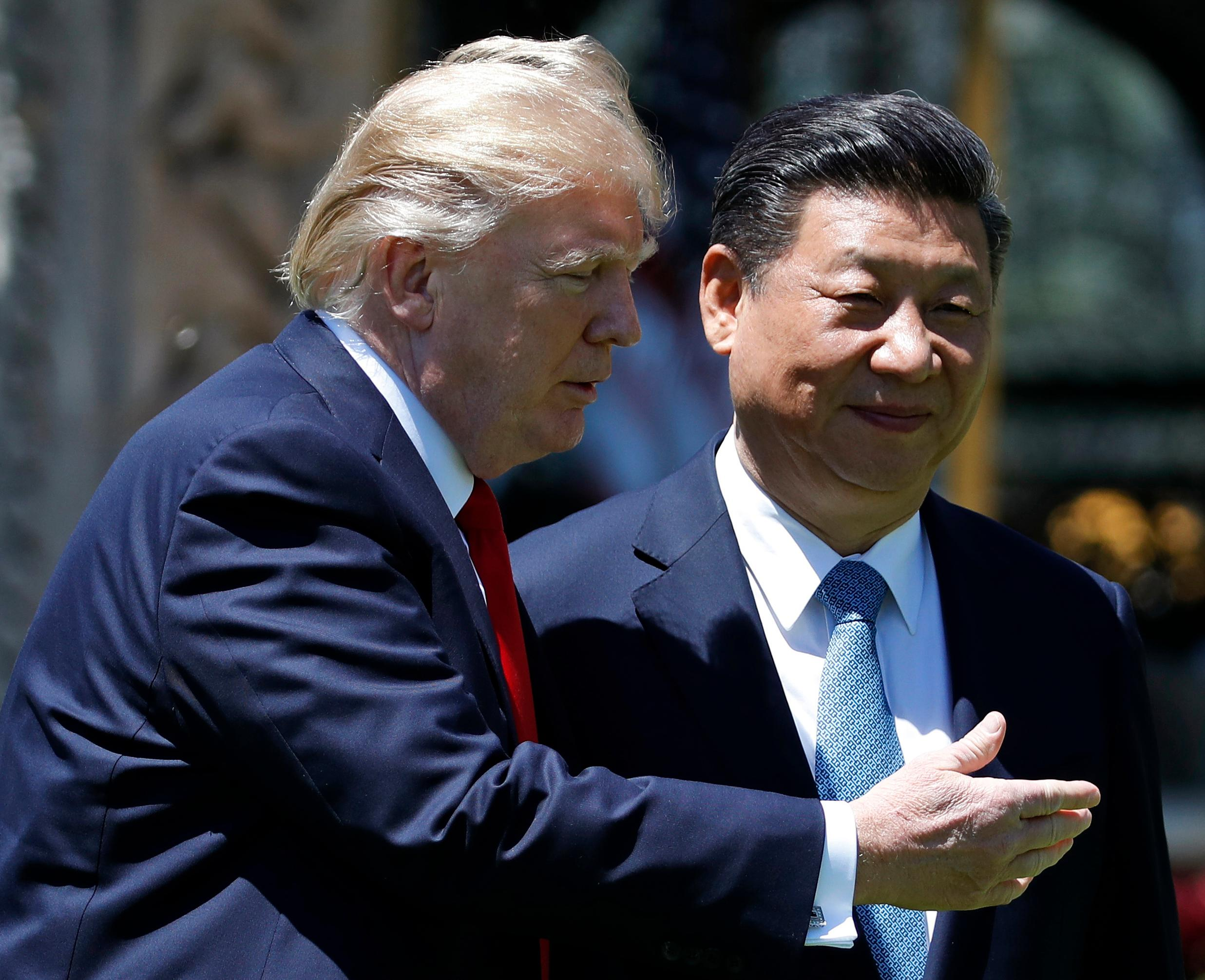 FILE - In this April 7, 2017, file photo, U.S. President Donald Trump gestures as he and Chinese President Xi Jinping walk together after their meetings at Mar-a-Lago in Palm Beach, Fla. After decades of failure to stop North Korea's march toward a nuclear arsenal, some see Trump's bluster as a shrewd attempt to press China, the North's most important ally and trading partner, into pressuring North Korea more aggressively over its nuclear program. (AP Photo/Alex Brandon, File)