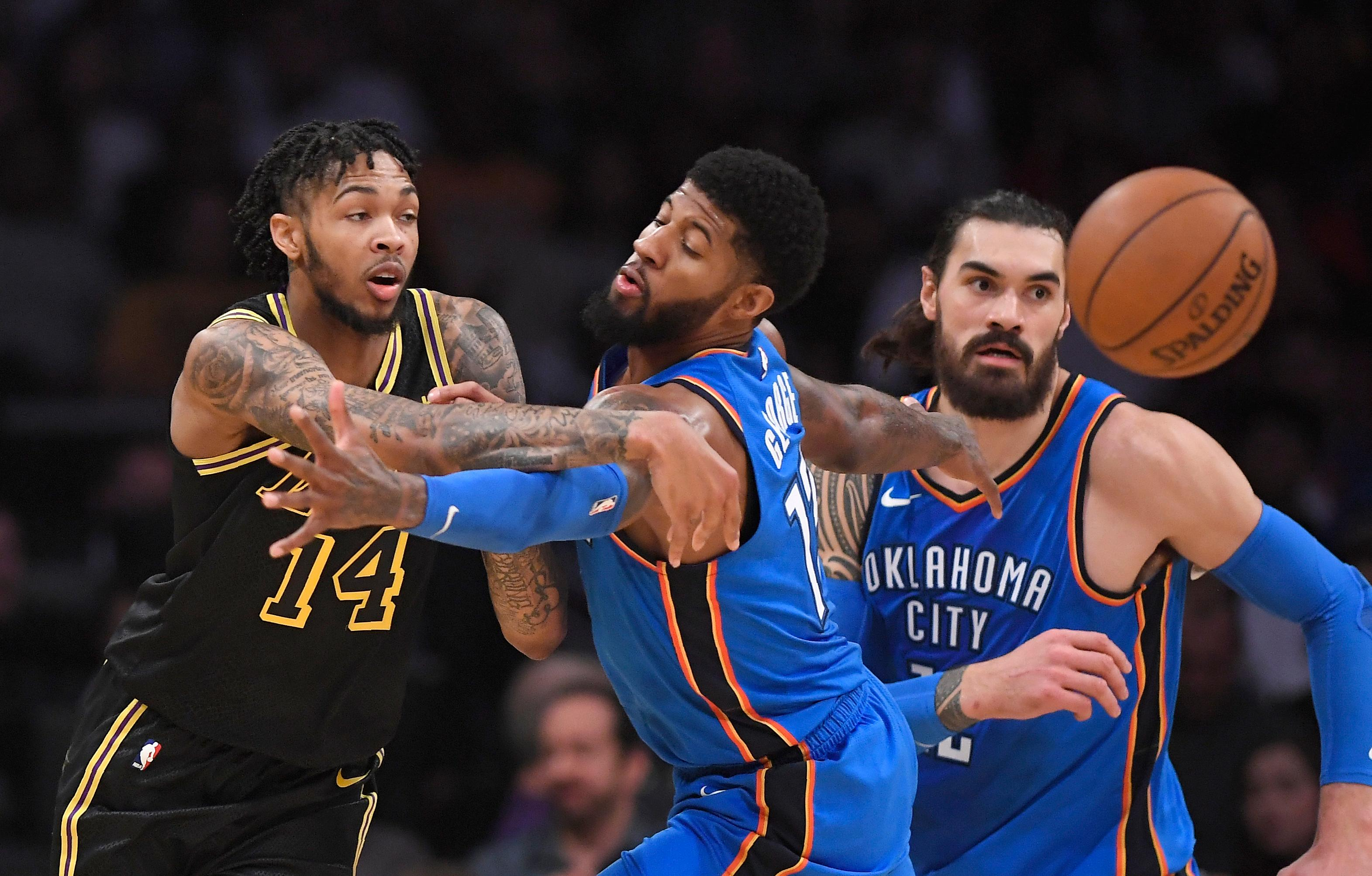 Los Angeles Lakers forward Brandon Ingram, left, passes the ball past Oklahoma City Thunder forward Paul George, center, and center Steven Adams, of New Zealand, during the first half of an NBA basketball game, Thursday, Feb. 8, 2018, in Los Angeles. (AP Photo/Mark J. Terrill)