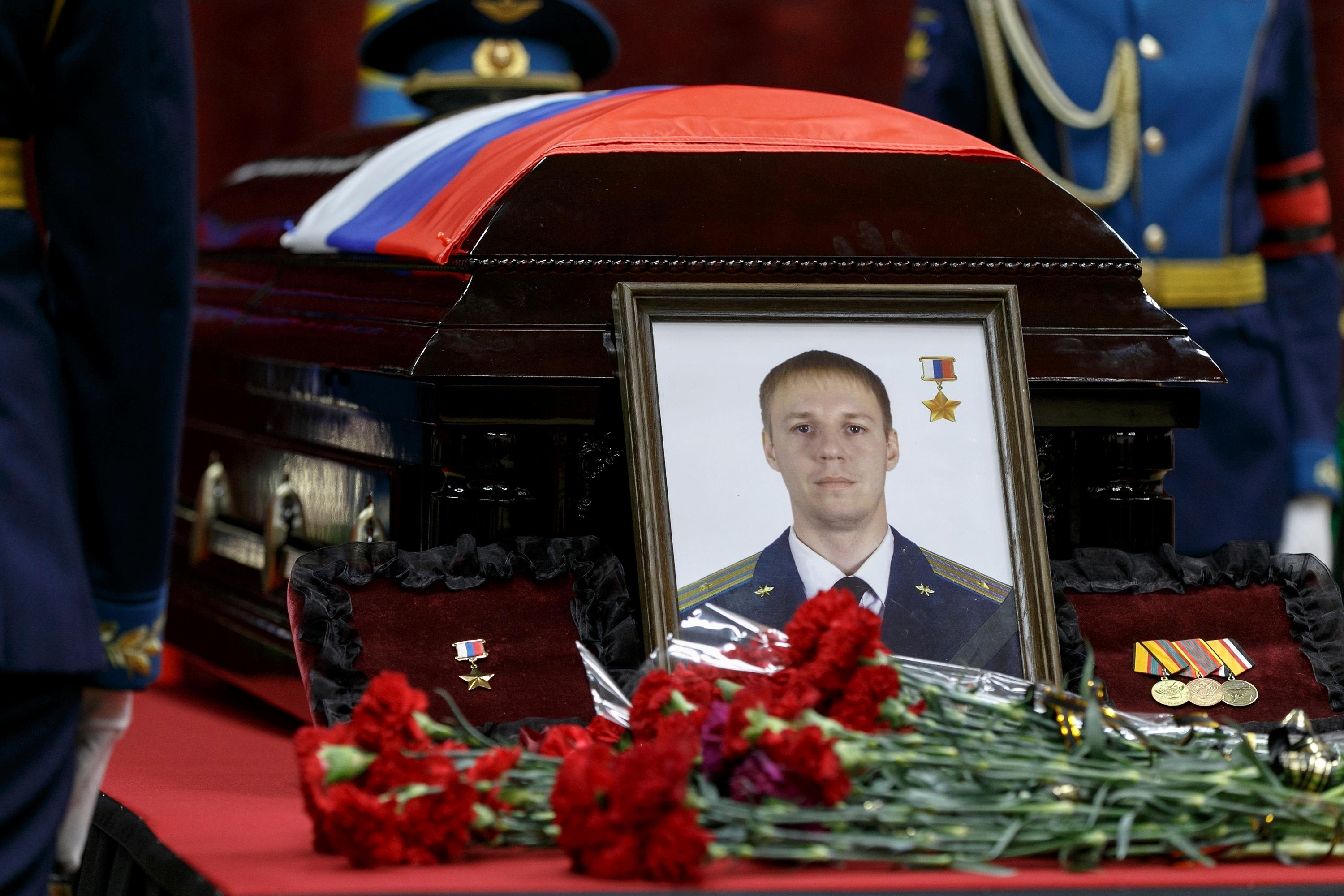 Russian honorary guards stand next to a coffin with the body of Russian Roman Filipov, the pilot of the Su-25 jet who ejected after Syrian insurgents shot down his plane traded fire with militants on the ground and then blew himself up to avoid being captured, during a funeral service in Voronezh, Russia, Thursday, Feb. 8, 2018. (Vadim Savitsky/Pool Photo via AP)