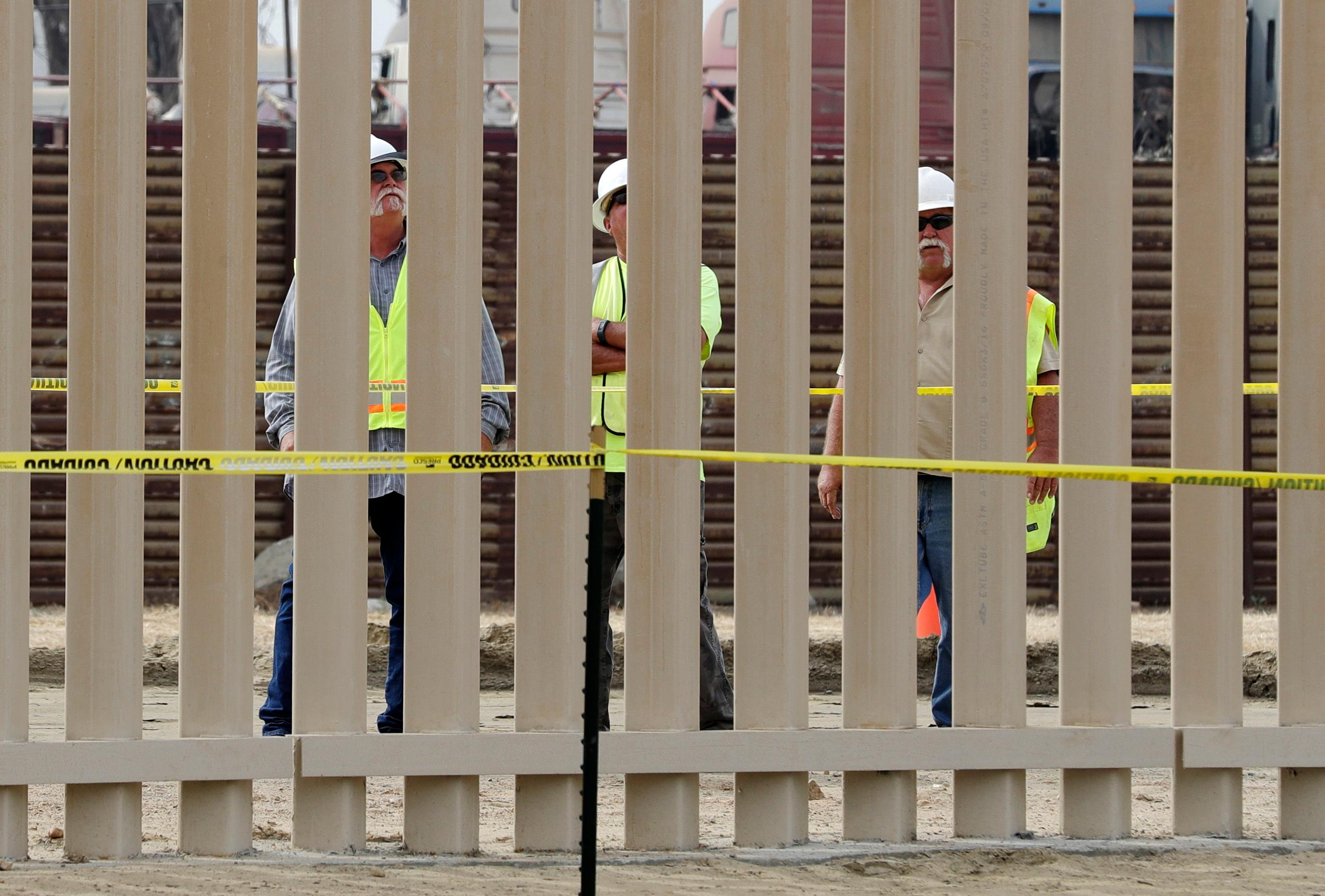 Crews look through a border wall prototype near the border with Tijuana, Mexico, Thursday, Oct. 19, 2017, in San Diego. Companies are nearing an Oct. 26 deadline to finish building eight prototypes of President Donald Trump's proposed border wall with Mexico. (AP Photo/Gregory Bull)