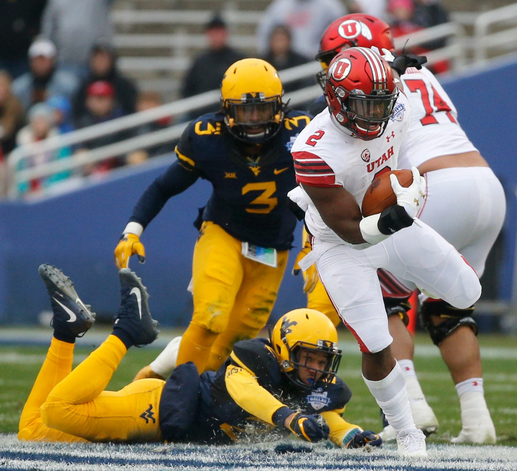 CORRECTS DAY TO TUESDAY Utah running back Zack Moss (2) runs the ball against West Virginia during the first half of Zaxby's Heart of Dallas Bowl at Cotton Bowl Stadium in Dallas on Tuesday, Dec. 26, 2017. (Rose Baca/The Dallas Morning News via AP)