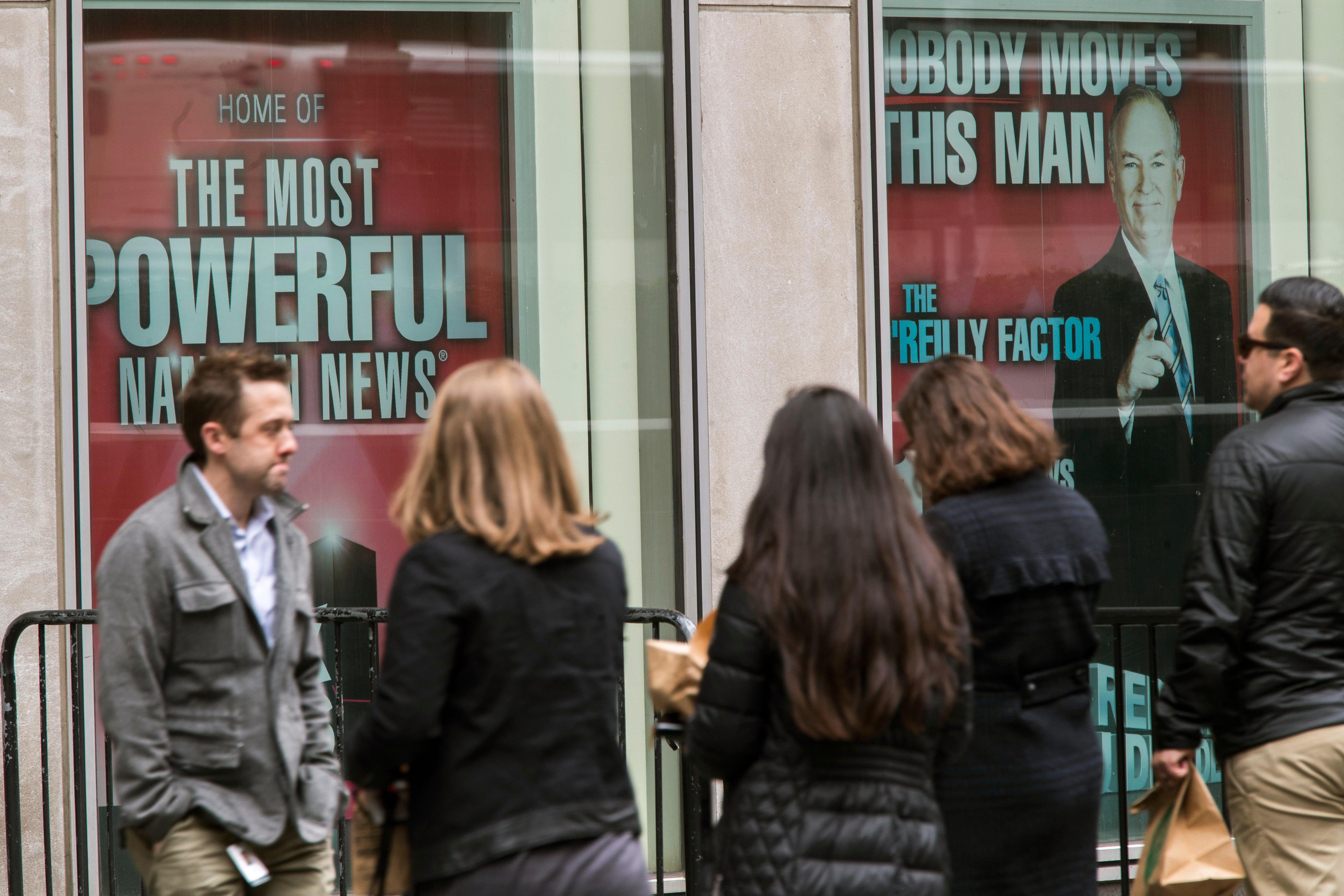 "People walk past posters featuring Bill O'Reilly as they enter the News Corp. headquarters in New York, Wednesday, April 19, 2017. O'Reilly has lost his job at Fox News Channel following reports that five women had been paid millions of dollars to keep quiet about harassment allegations. 21st Century Fox issued a statement Wednesday that ""after a thorough and careful review of the allegations, the company and Bill O'Reilly have agreed that Bill O'Reilly will not be returning to the Fox News Channel.  (AP Photo/Mary Altaffer)"