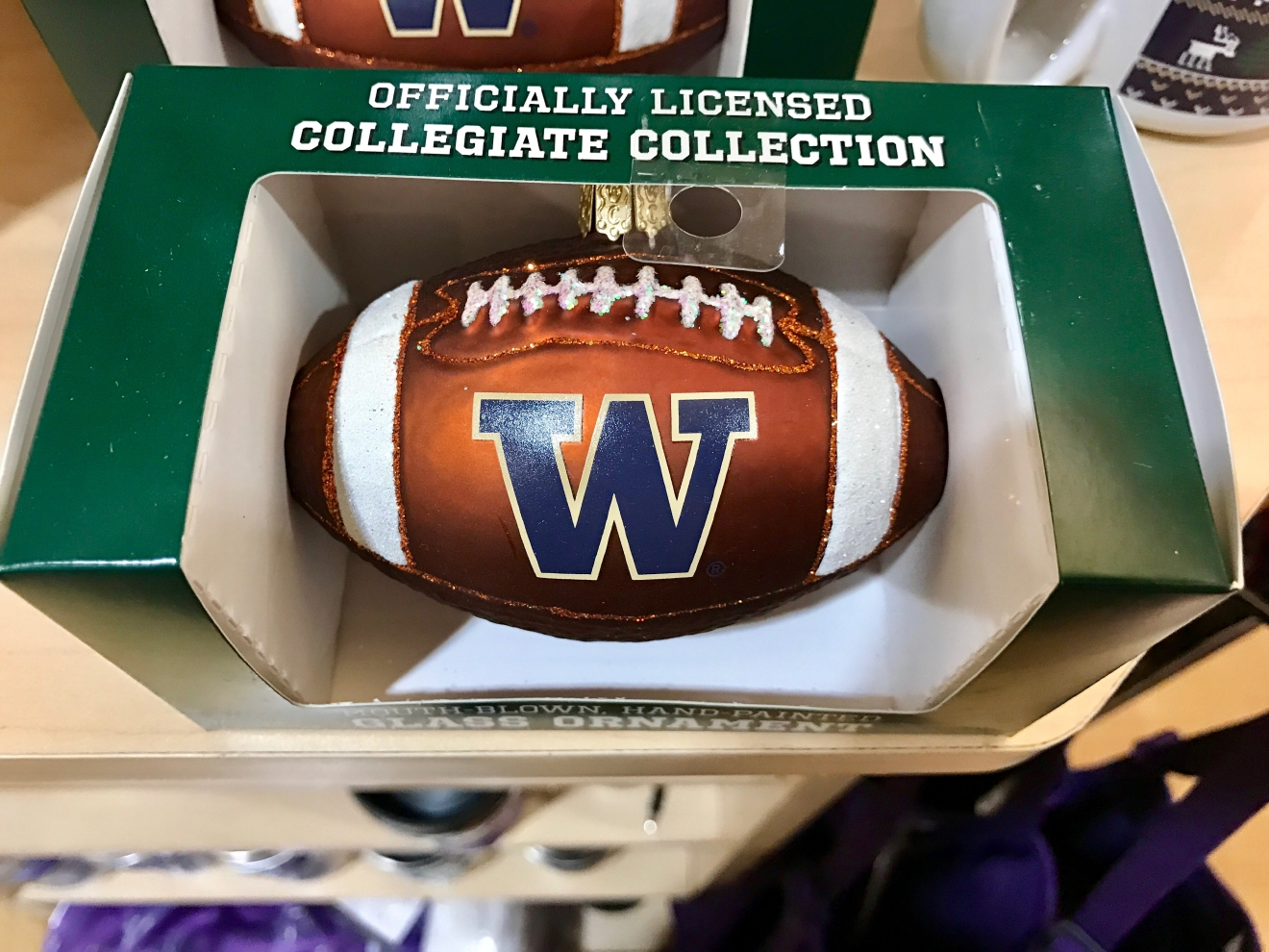UW Football Ornament - $14.99                                          Whether you're a current student, alum, or just *love* the Dawgs, it's a pretty exciting time to be a Husky fan right now. Just to catch you up, the University of Washington football team is having one of their best seasons in years, and will be playing the Peach Bowl in Atlanta on December 31st. If you know a Dawg fan, they're probably salivating at the mouth right about now. Which is why it's a perfect time to give them a themed gift! Here are some of the coolest Husky gear we saw at the University Bookstore on the Avenue during our last visit. Pro Tip: They're open 10 a.m. - 7 p.m. on Christmas Eve! (Image: Britt Thorson / Seattle Refined)