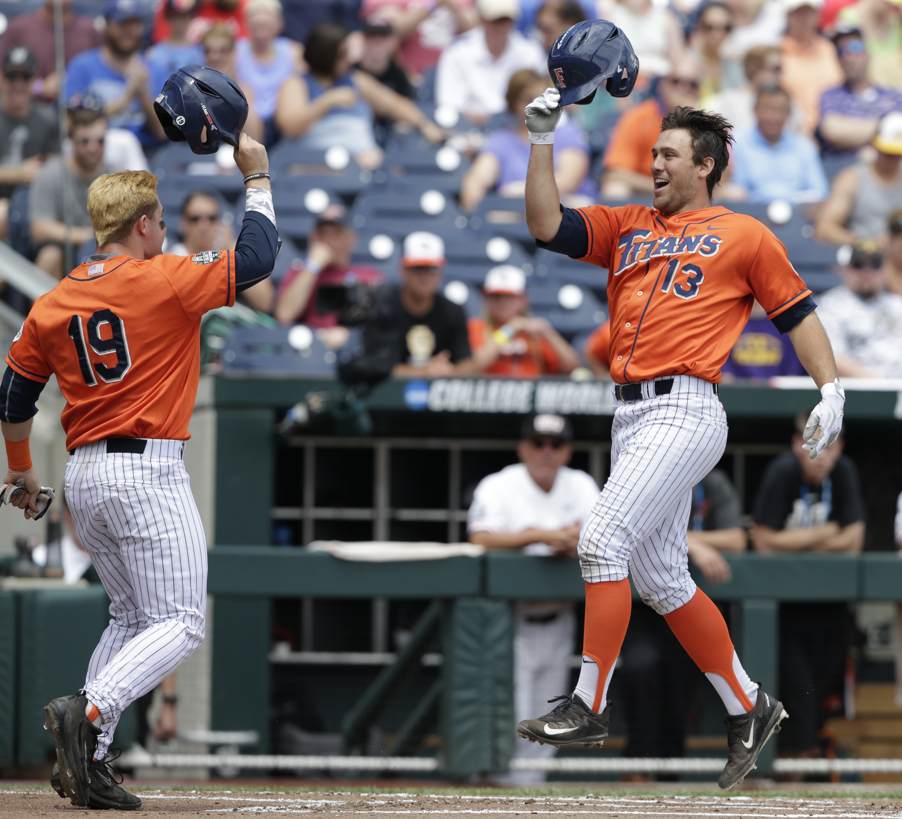 Cal State Fullerton's Timmy Richards (13) celebrates with Dillon Persinger (19) after his three-run home run in the first inning of an NCAA mens College World Series baseball game against Oregon State in Omaha, Neb., Saturday, June 17, 2017. (AP Photo/Nati Harnik)