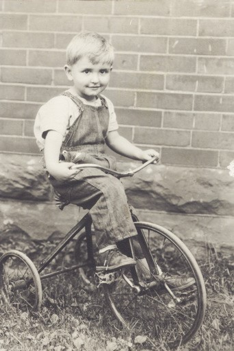 Young Tommy S. Monson taking a spin on trike.  (Photo: MormonNewsroom.org)