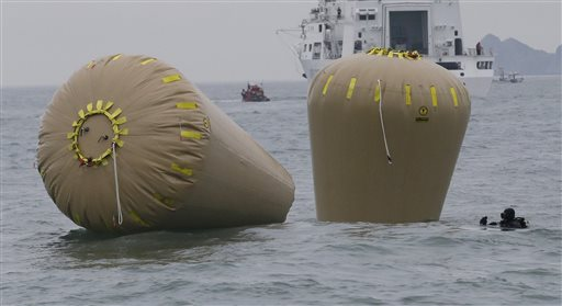 A rescue diver swims near the buoys installed to mark the sunken 6,852-ton ferry Sewol in the water off the southern coast near Jindo, south of Seoul, South Korea, Friday.