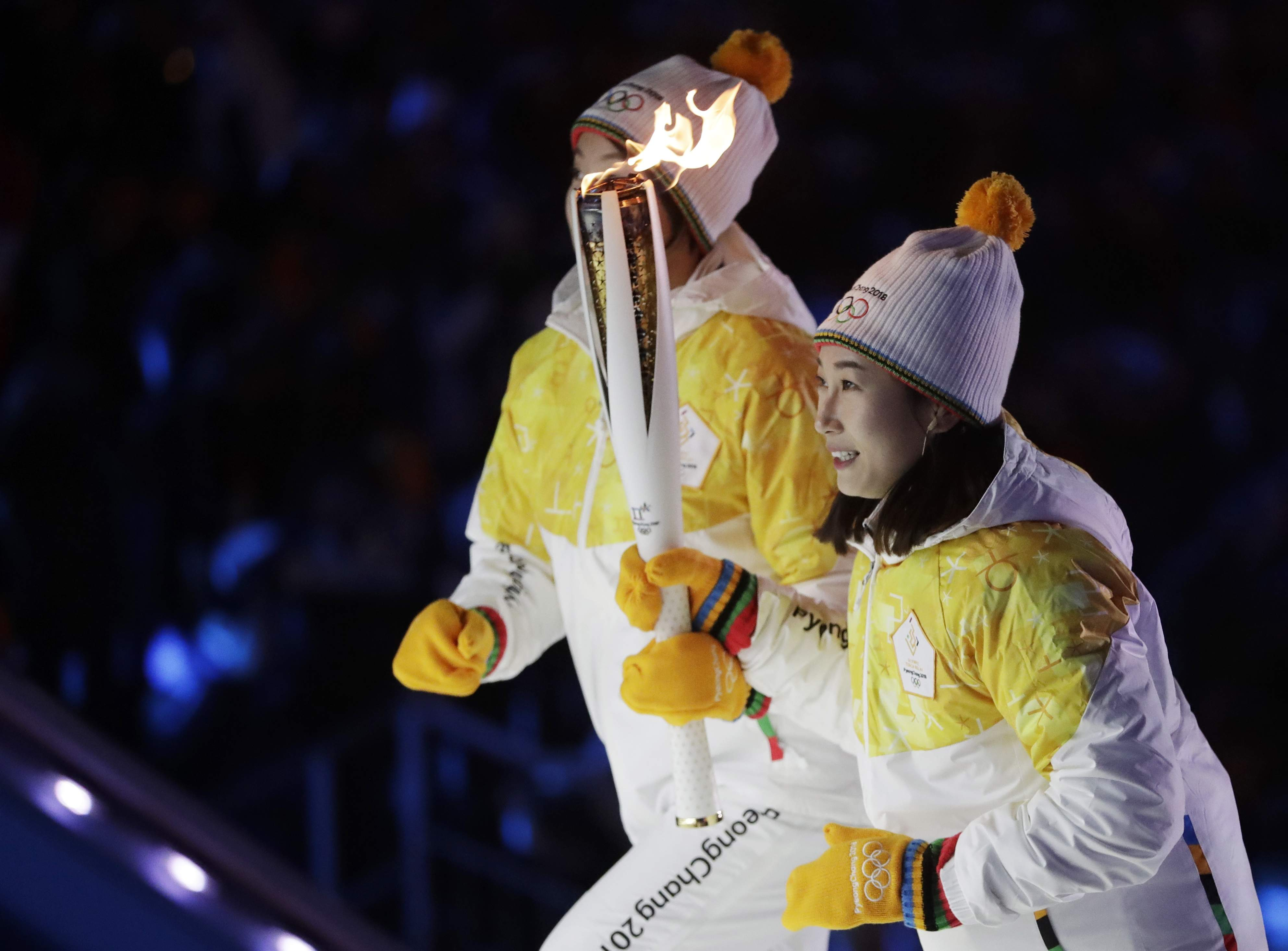 North Korea's Jong Su Hyon, left, and South Korea's Park Jong-ah carry the torch in the stadium during the opening ceremony of the 2018 Winter Olympics in Pyeongchang, South Korea, Friday, Feb. 9, 2018. (AP Photo/Matthias Schrader)